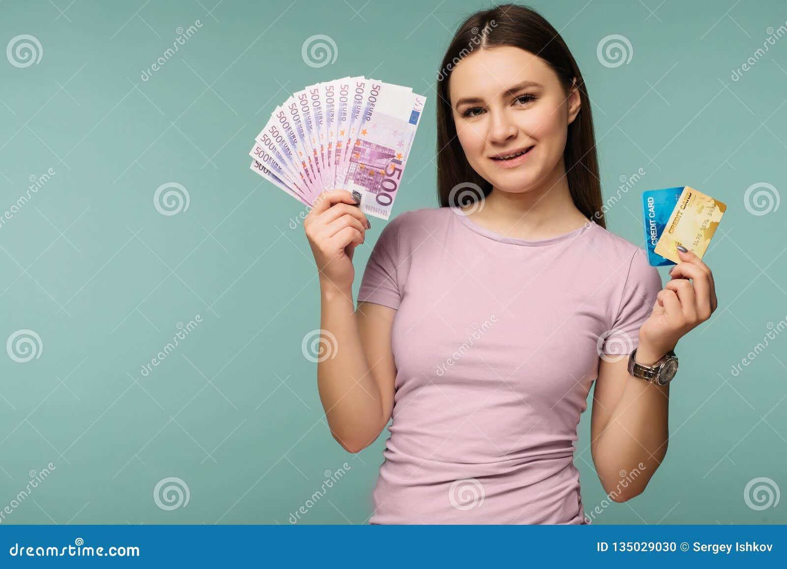 Foto de la mujer morena caucásica 20s que sonríe mientras que sostiene la tarjeta de crédito y la fan del efectivo euro aisladas