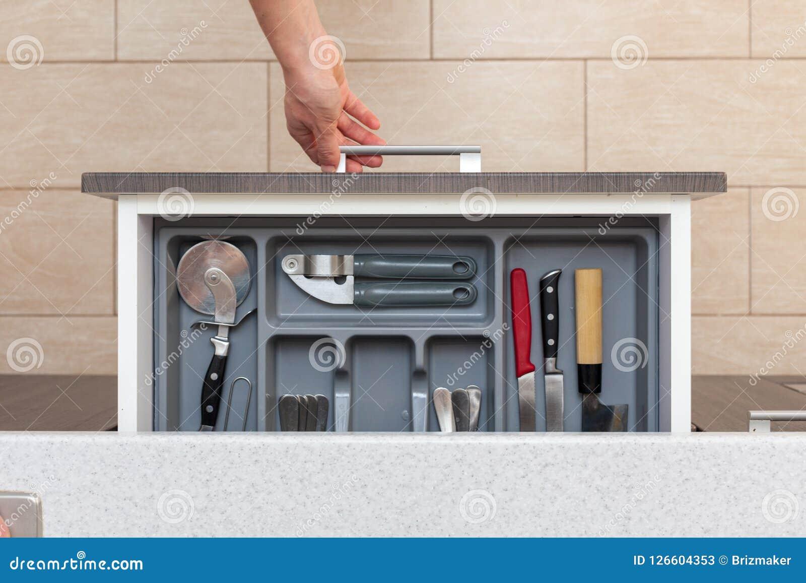 Foto de la opinión superior del alto ángulo del cajón abierto de la cocina de la mano de la mujer por d