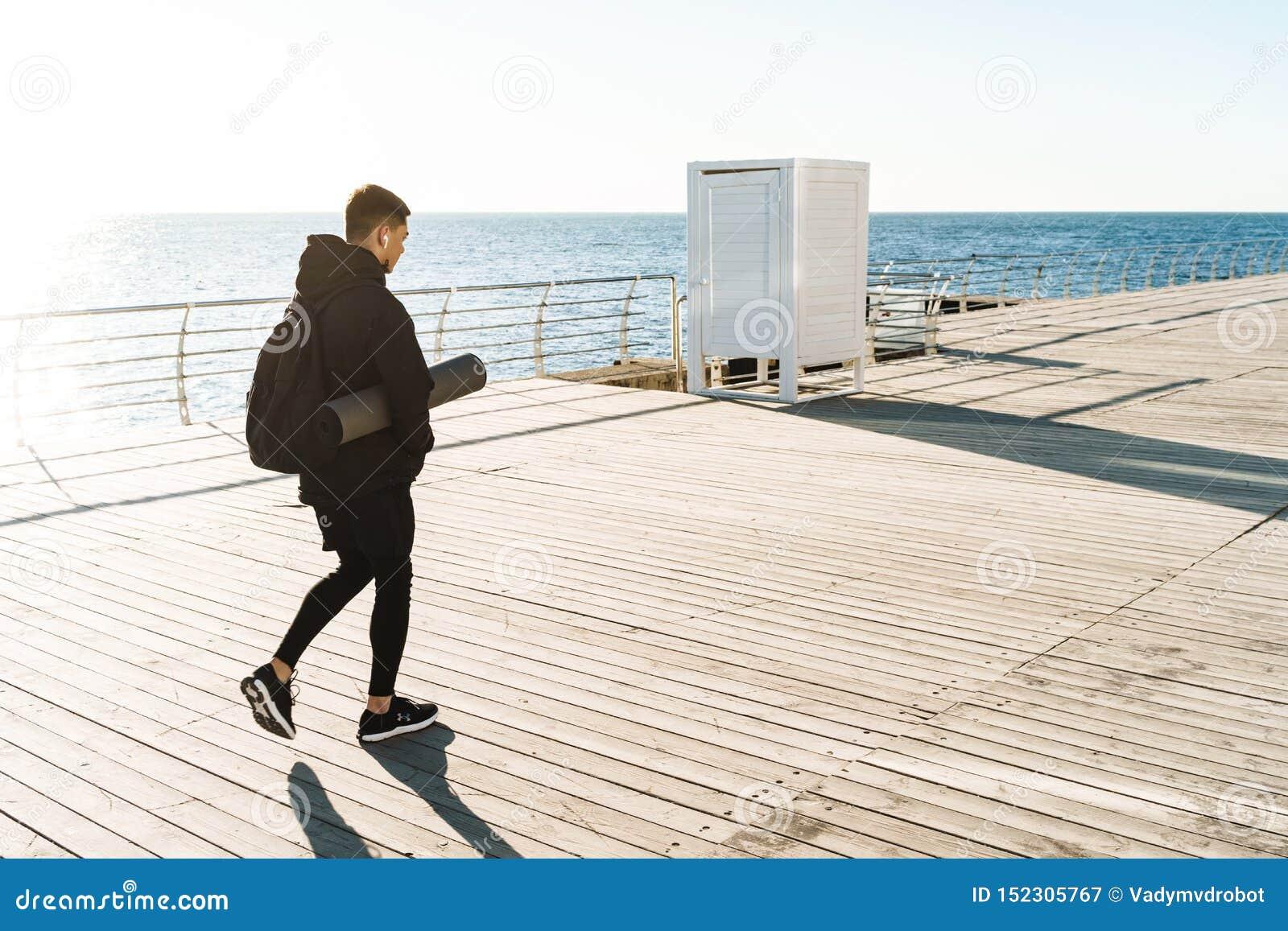 Foto de los earpods que llevan del deportista atlético que caminan por la playa después de entrenamiento de la mañana
