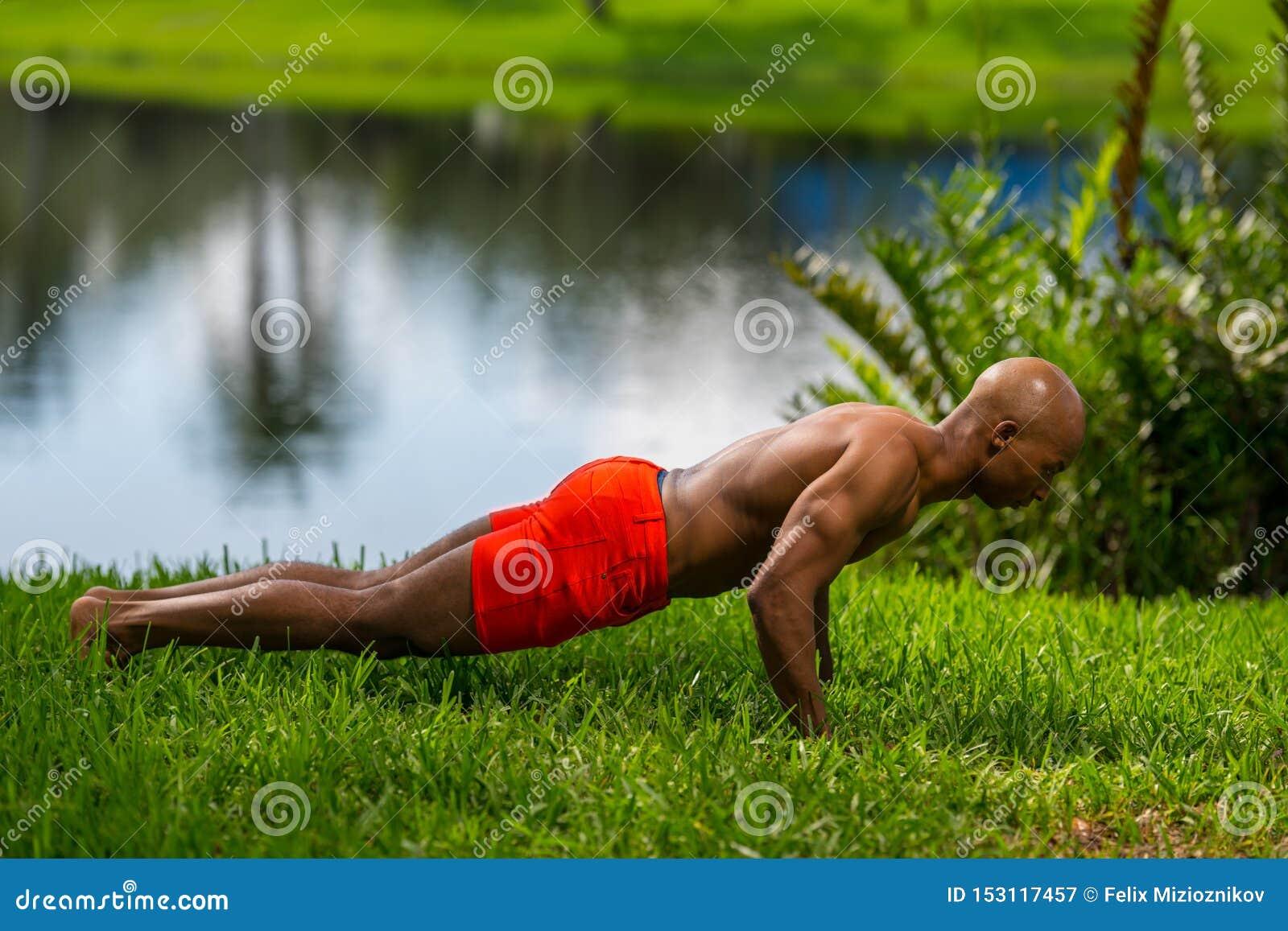 Foto de um modelo da aptidão que levanta a prancha na grama