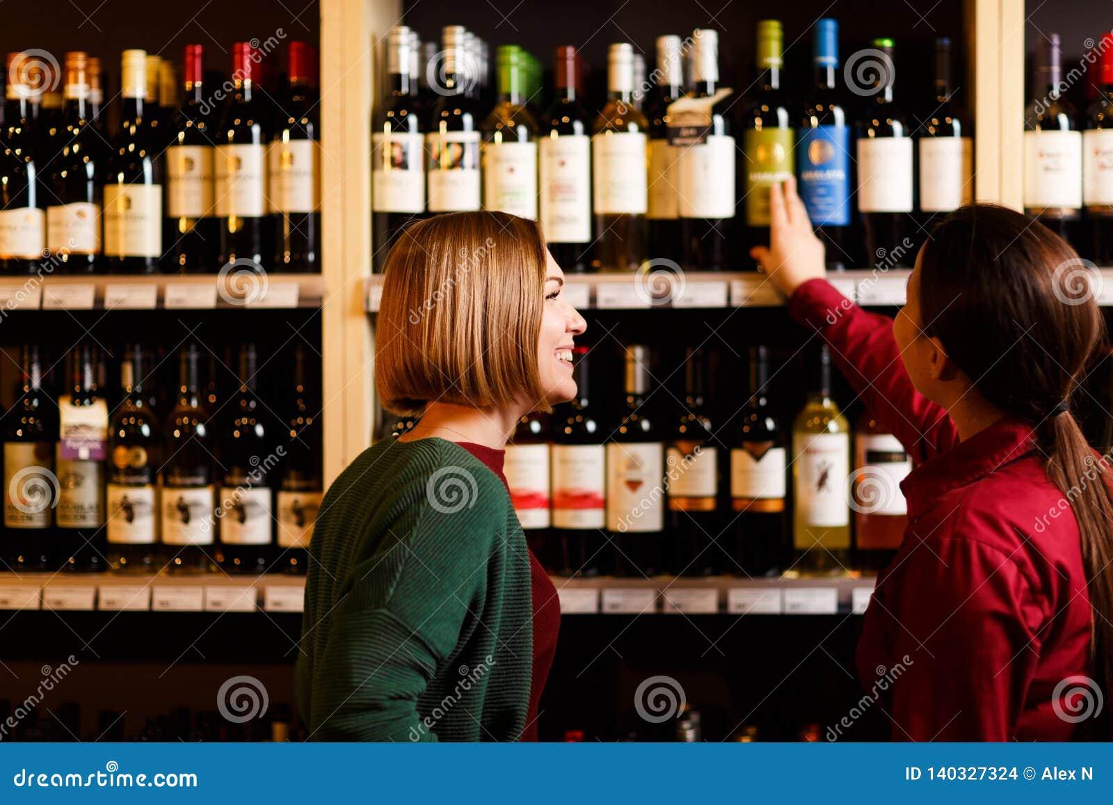 Foto de uma parte traseira de duas jovens mulheres na loja de vinhos