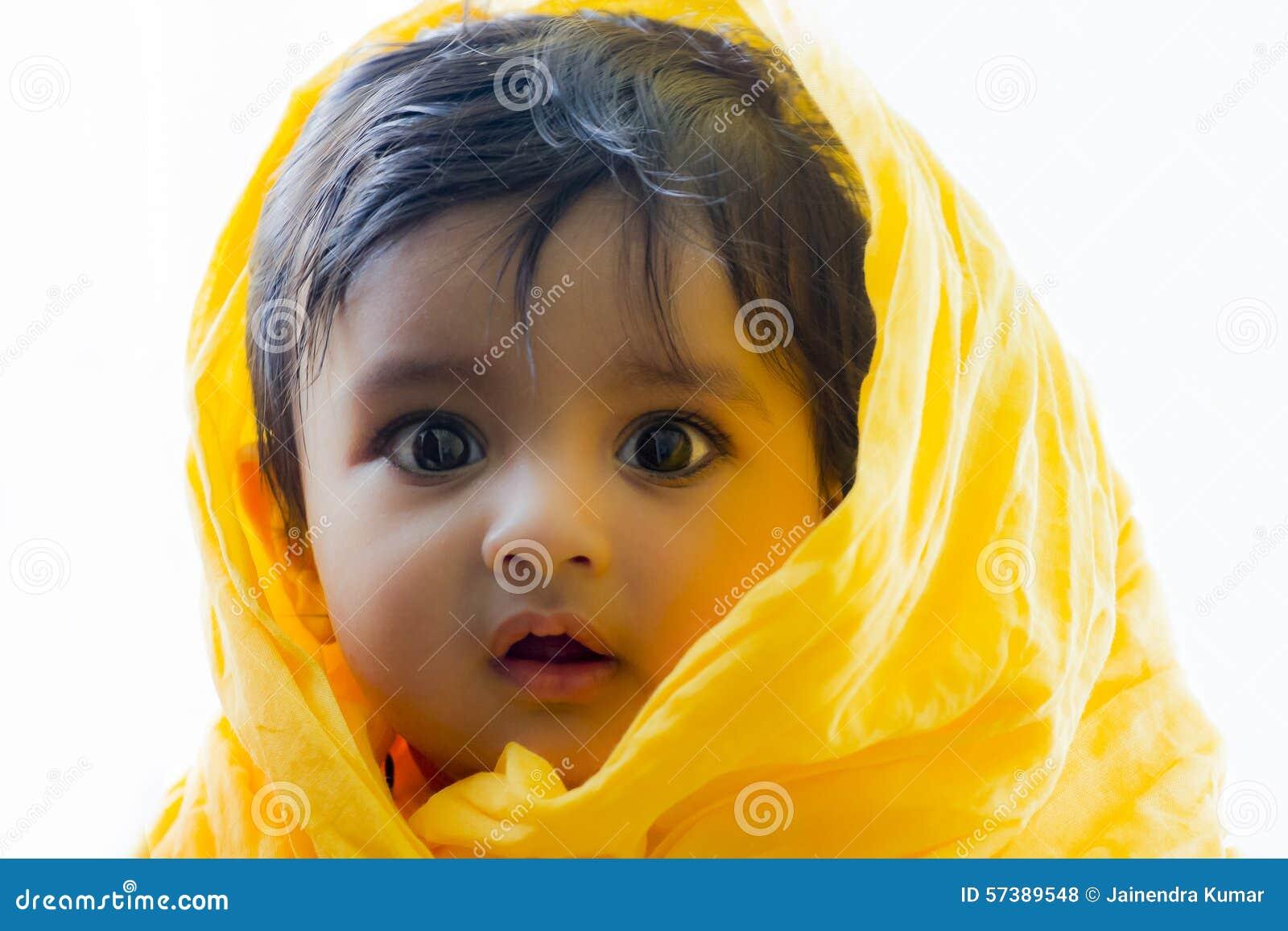 Foto del bebé indio lindo y feliz con los ojos expresivos