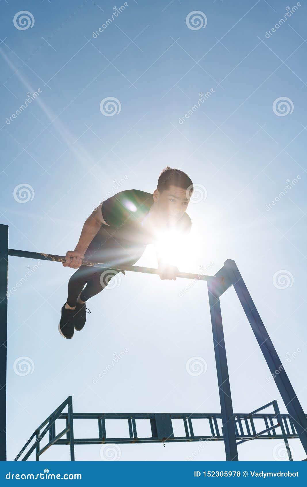 Foto del deportista atlético que hace la acrobacia en barra gimnástica horizontal durante entrenamiento de la mañana por la playa