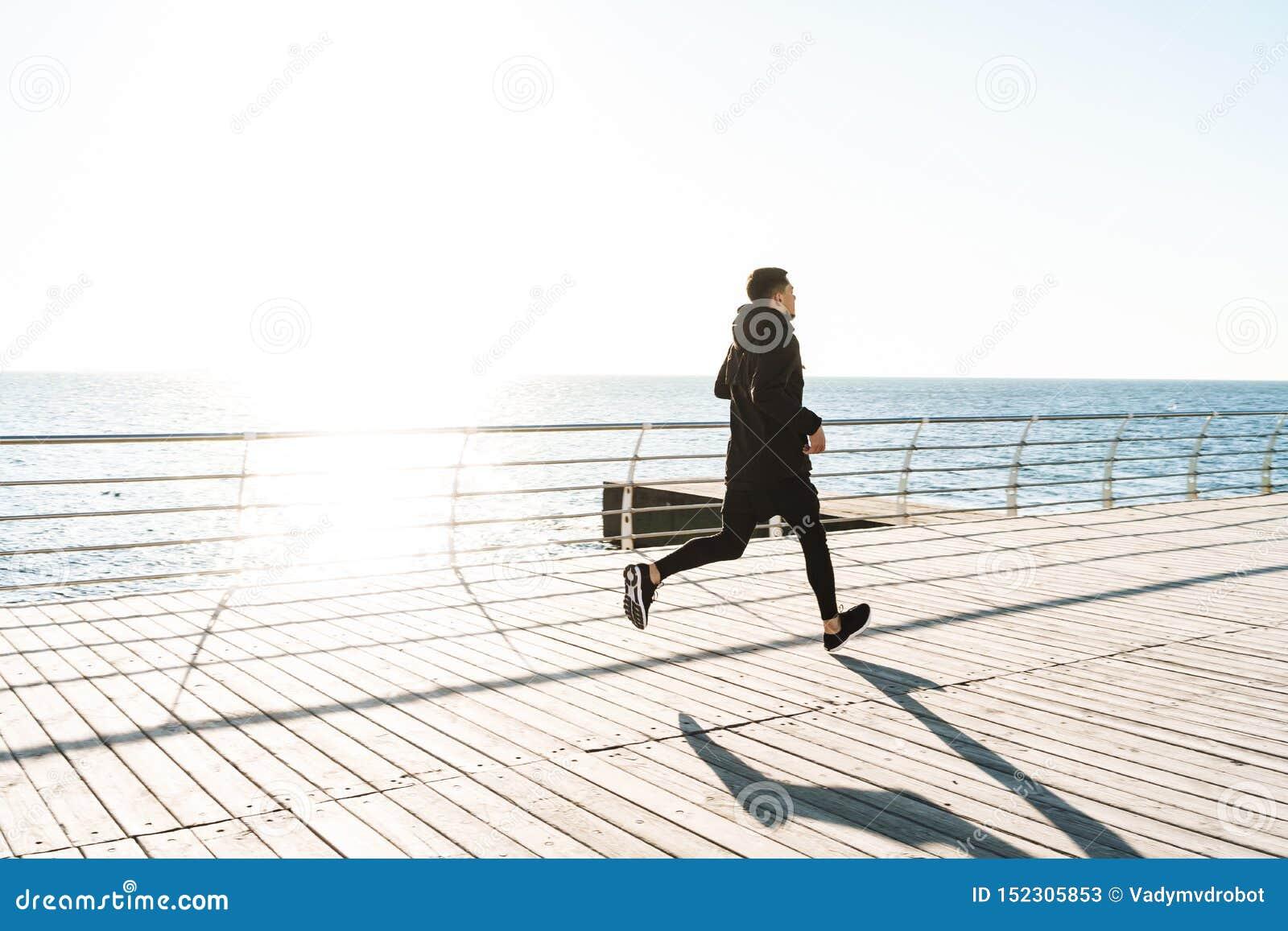 Foto del deportista sano que corre por la playa a lo largo del paseo marítimo de madera durante entrenamiento de la mañana