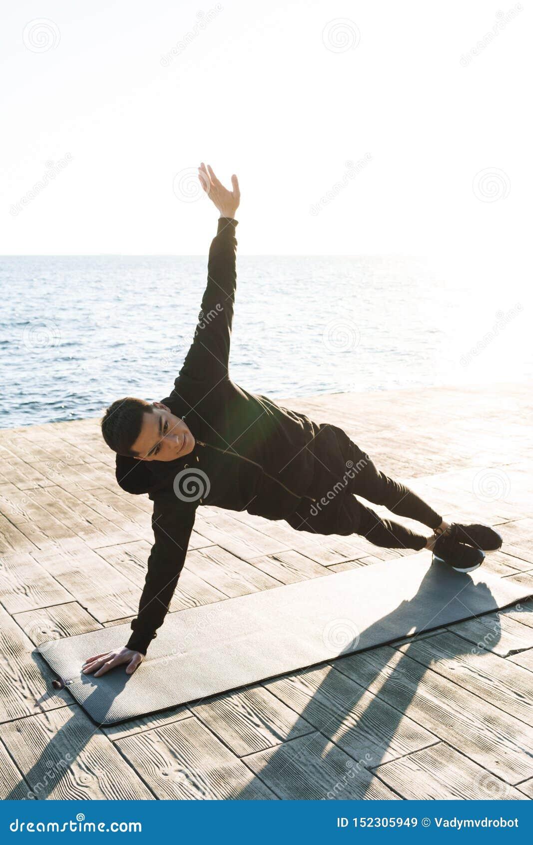 Foto del deportista satisfecho 20s en el chándal que miente en la estera de la aptitud y que hace ejercicio del tablón por la pla