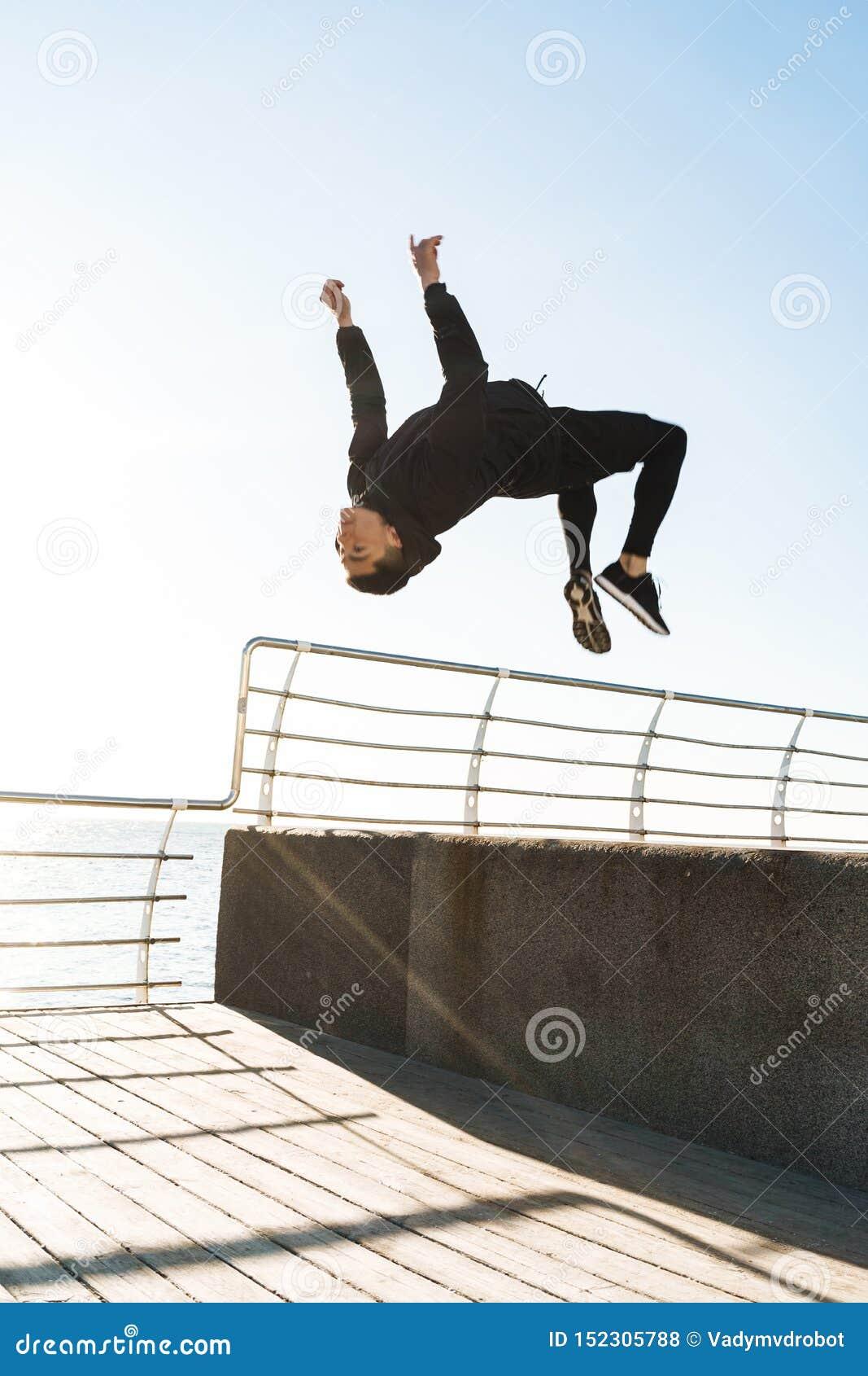 Foto del hombre atlético que hace la acrobacia y que salta durante entrenamiento de la mañana por la playa
