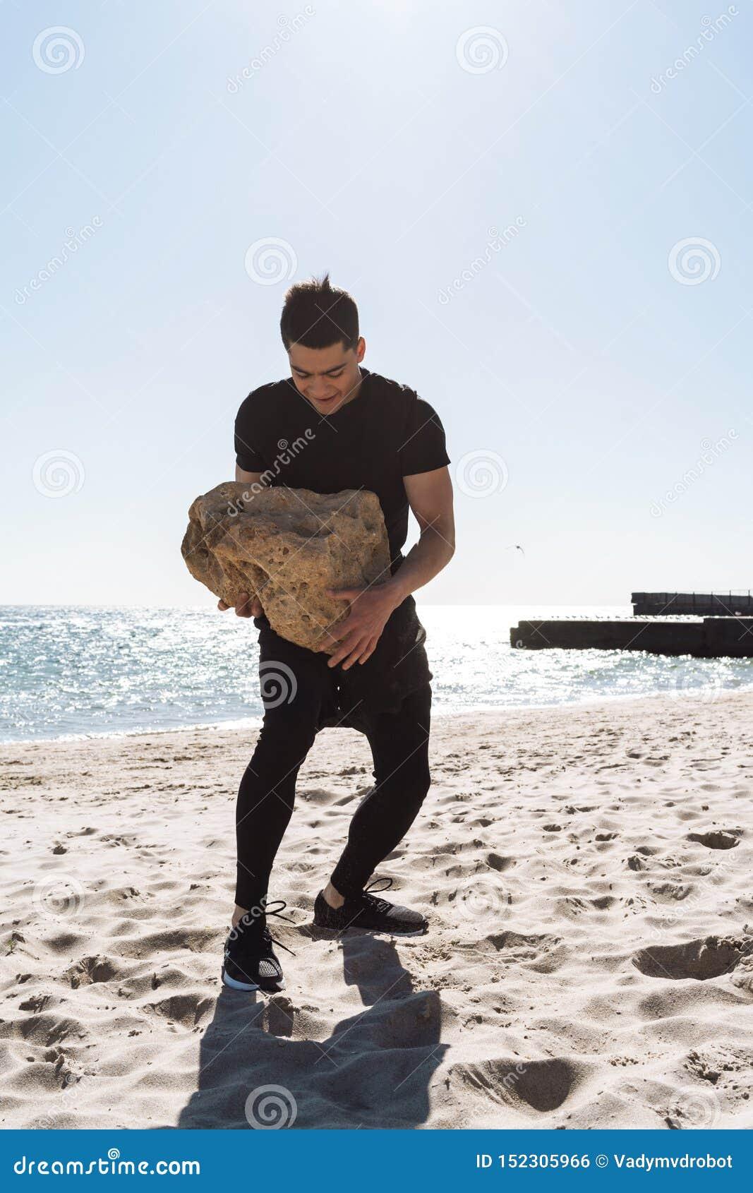 Foto del hombre moreno fuerte que camina a lo largo de la playa por la playa y de la piedra grande que lleva en sus manos