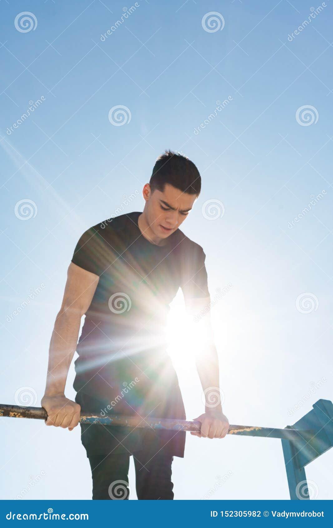 Foto del individuo de la aptitud que hace la acrobacia en barra gimnástica horizontal durante entrenamiento de la mañana por la p