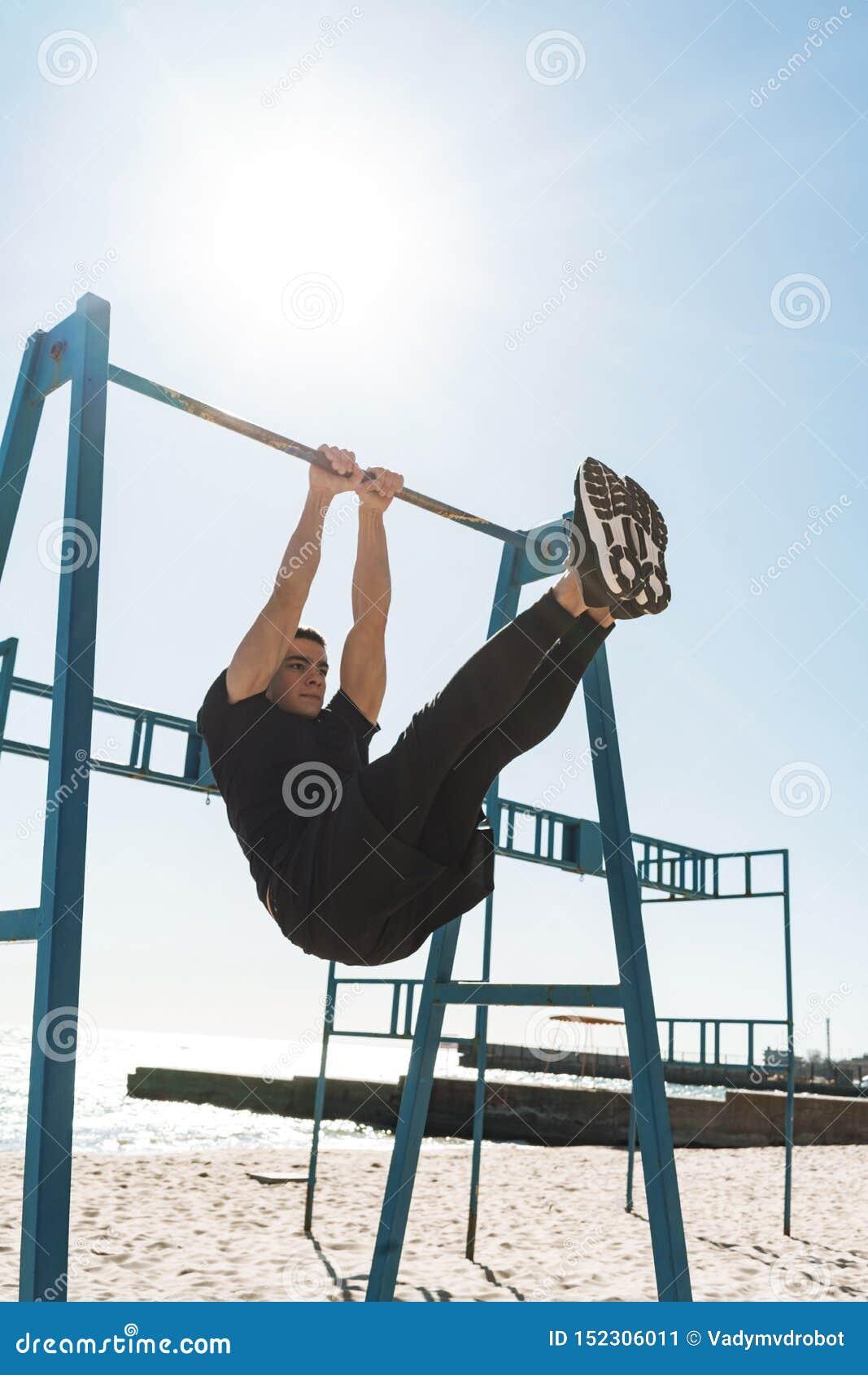 Foto del individuo hermoso que hace la acrobacia en barra gimnástica horizontal durante entrenamiento de la mañana por la playa