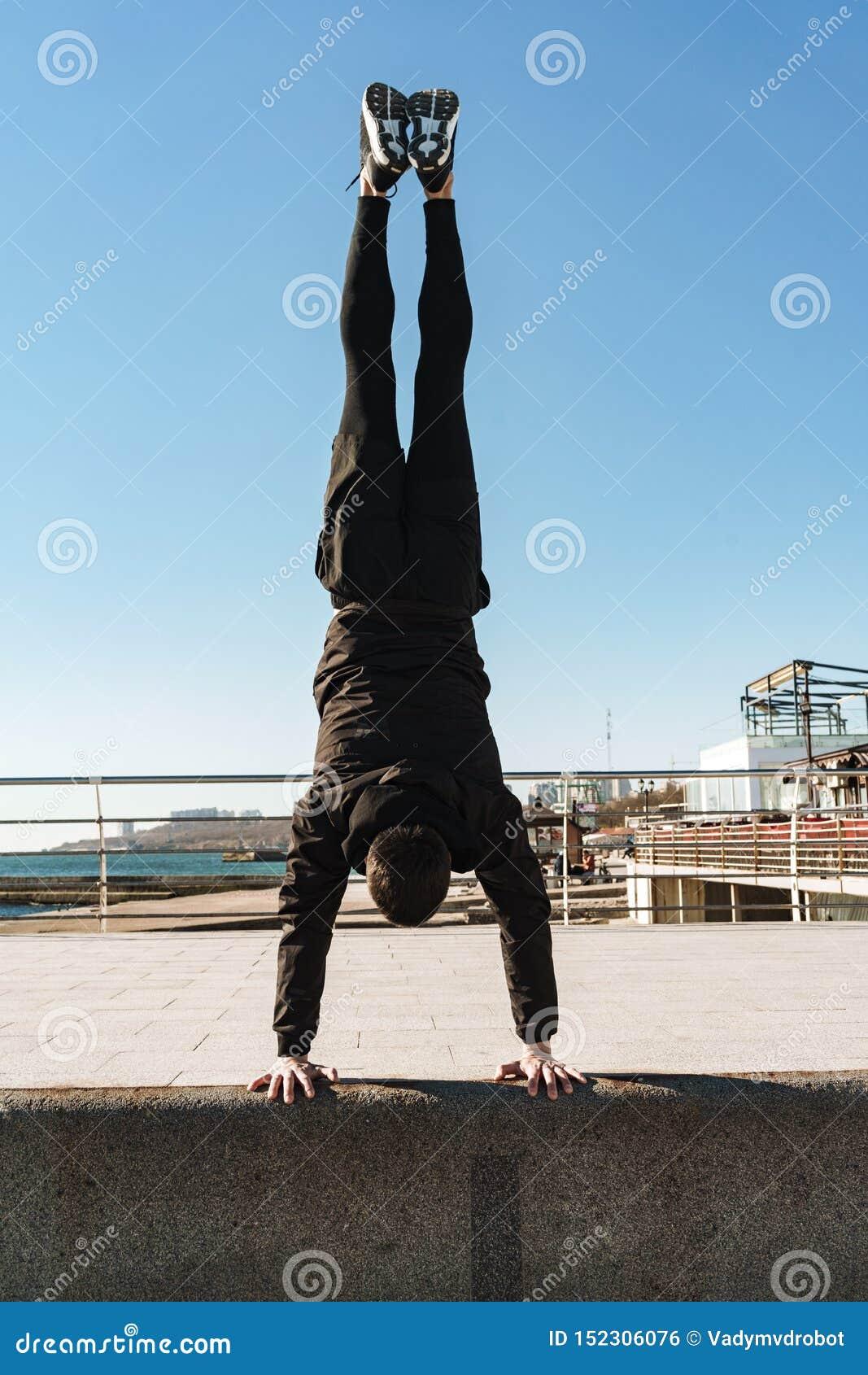 Foto del individuo del parkour que hace la acrobacia y que defiende en sus brazos durante entrenamiento de la mañana la playa