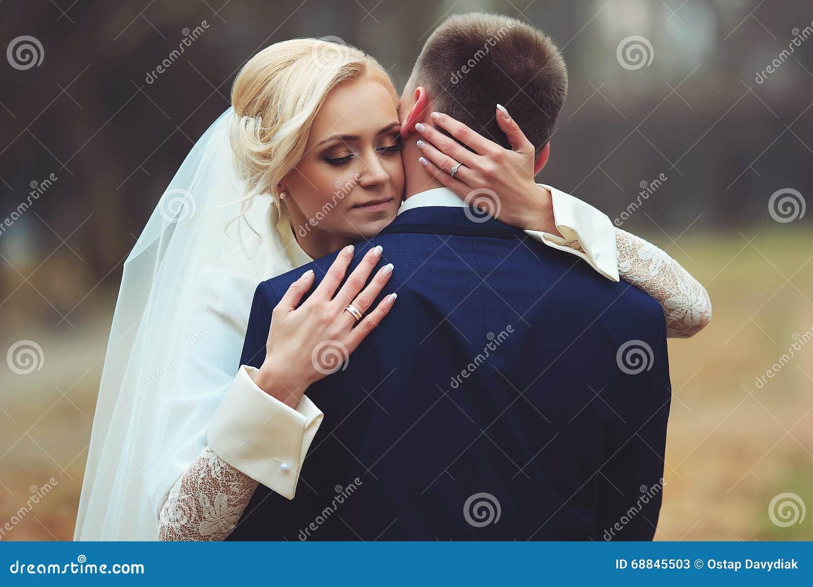 Foto del novio de abarcamiento de la novia hermosa de la parte posterior en el parque