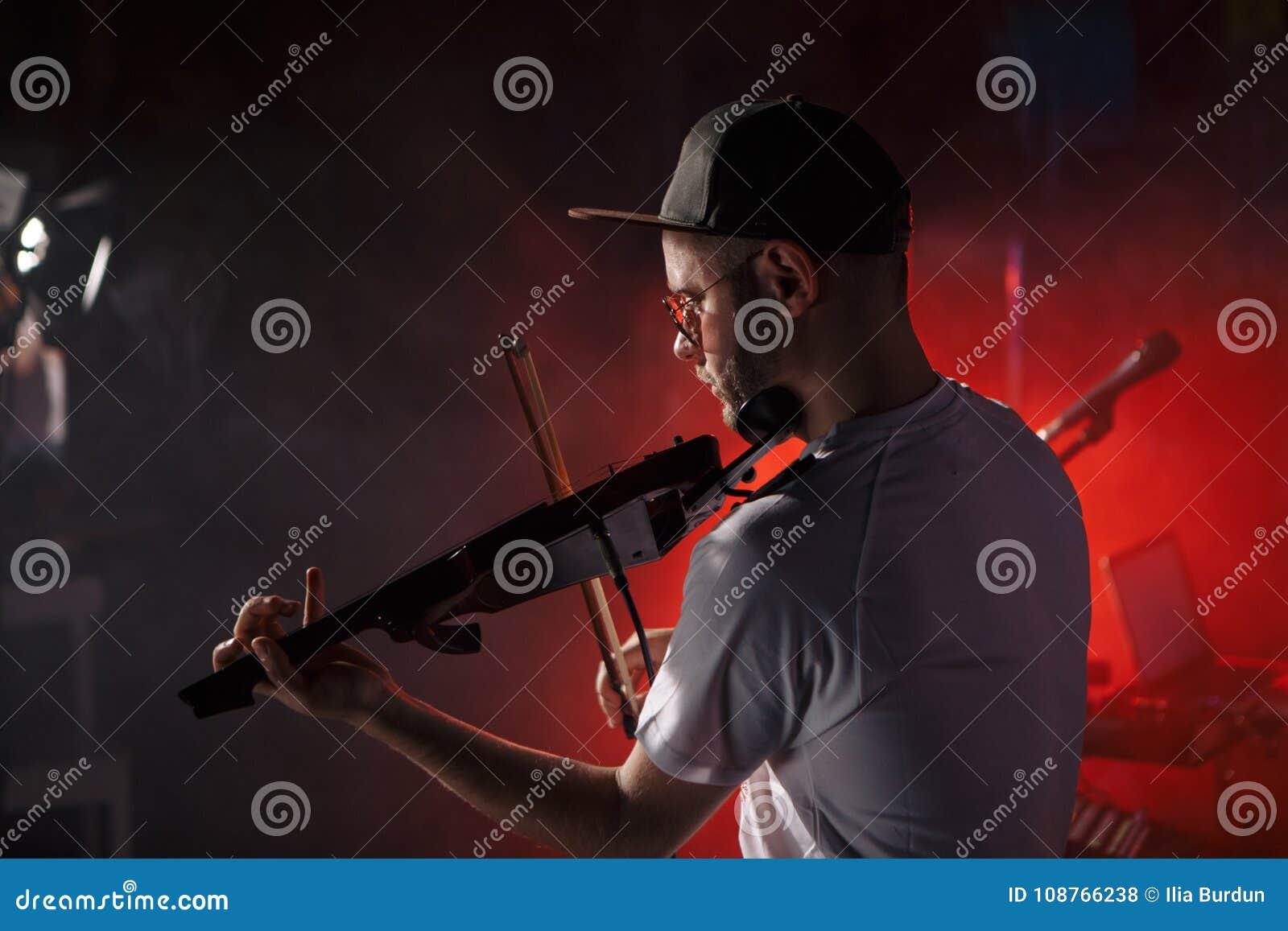 Foto del primer del hombre que toca el violín eléctrico