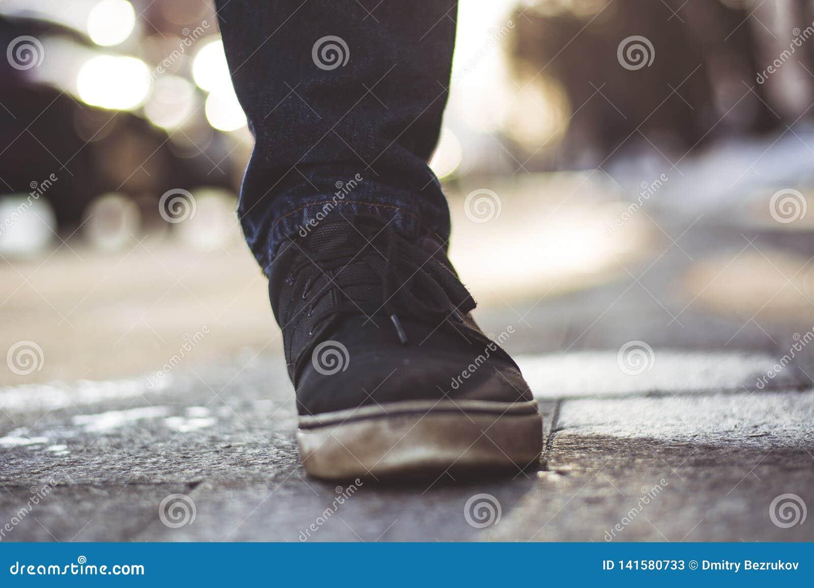 Foto del primo piano delle gambe degli uomini in scarpe da tennis nere