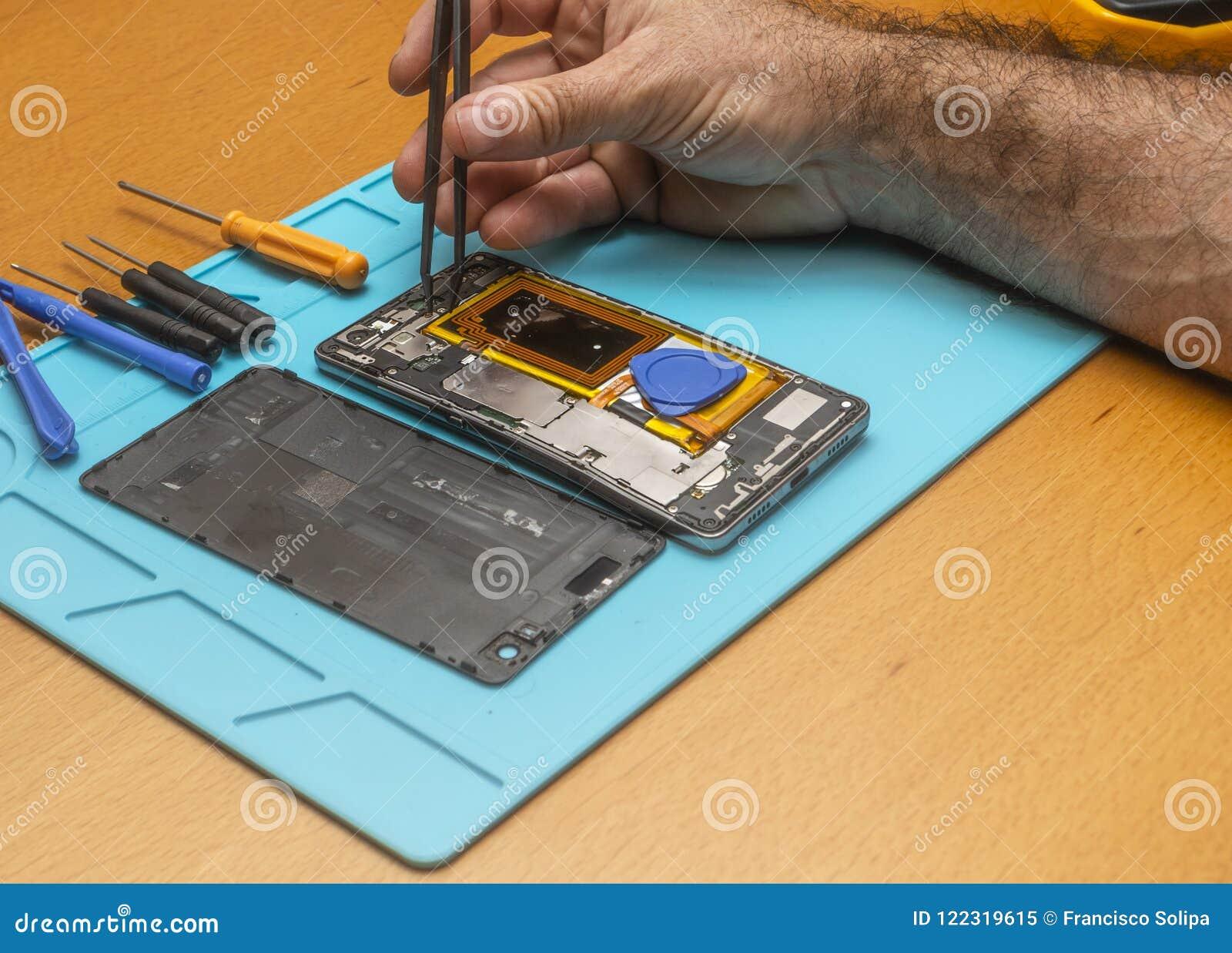 Foto del primo piano del tecnico Hand Repairing Cellphone