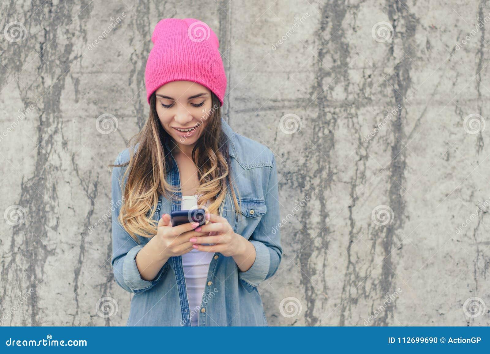 Foto del primo piano del testo sorridente della lettura della ragazza dei pantaloni a vita bassa sullo smartphone È molto felice