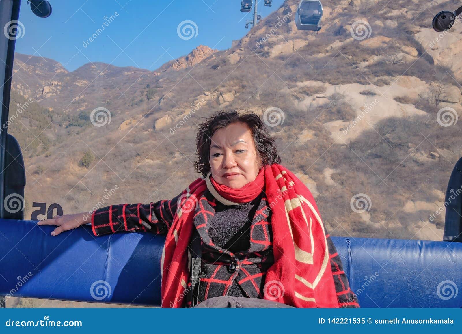 Foto del ritratto del viaggiatore asiatico senior delle donne che si siede sulla cabina di funivia per attraversare la montagna a