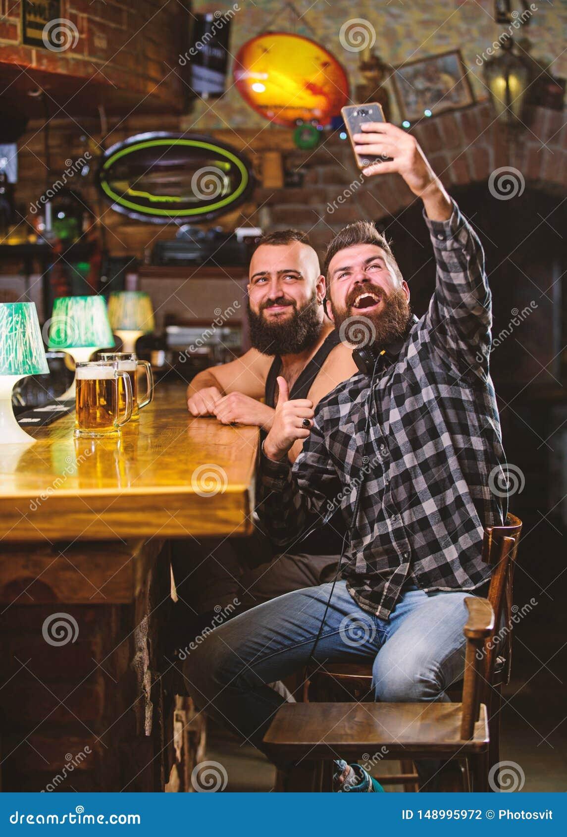 Foto del selfie de la toma para recordar la gran tarde en pub Comunicaci?n en l?nea Smartphone barbudo del control del inconformi
