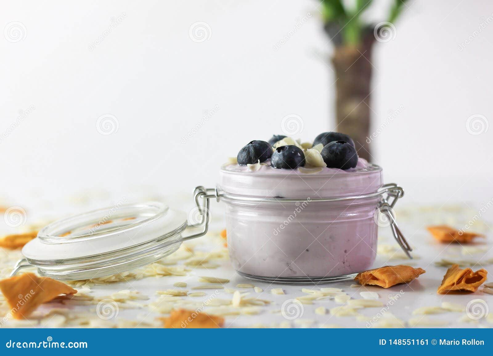 Foto del yogurt di mirtillo con le mandorle ed il mango secco, con il tronco brasiliano nei precedenti unfocused