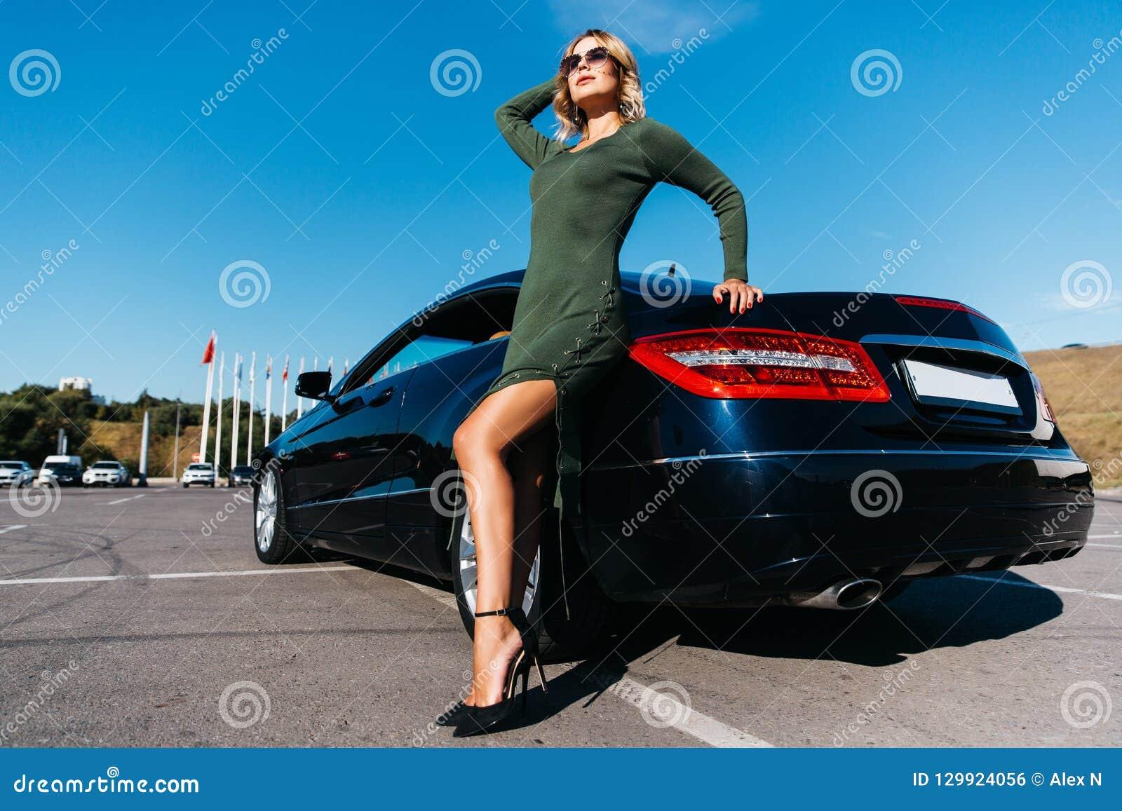 Foto della donna bionda sexy in occhiali da sole nella condizione lunga del vestito vicino all automobile nera con la porta apert