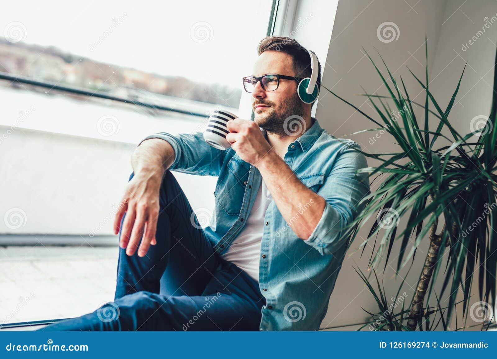 Foto dentro do homem satisfeito que olha através da janela e que escuta a música