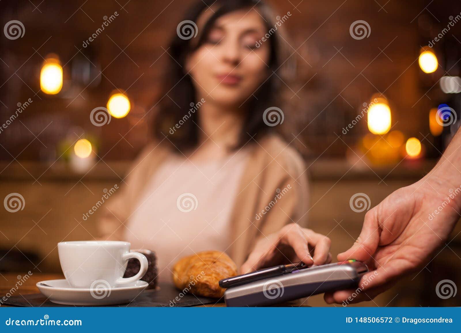 Foto der attraktiven Frau zahlend mit Handy unter Verwendung der drahtlosen Zahlung auf einer Kaffeestube