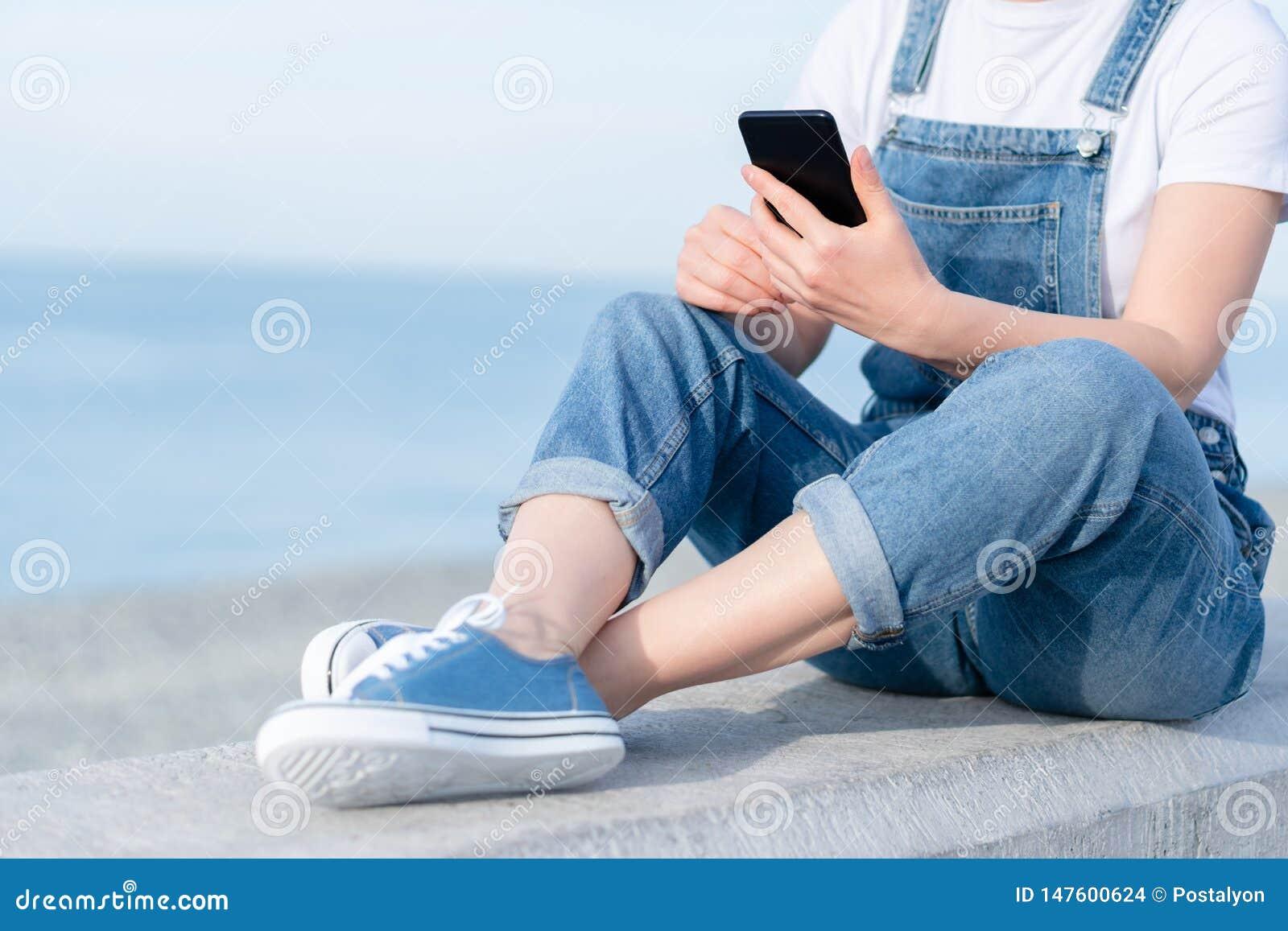 Foto der erwachsenen Frau unter Verwendung eines Handys während der Reise