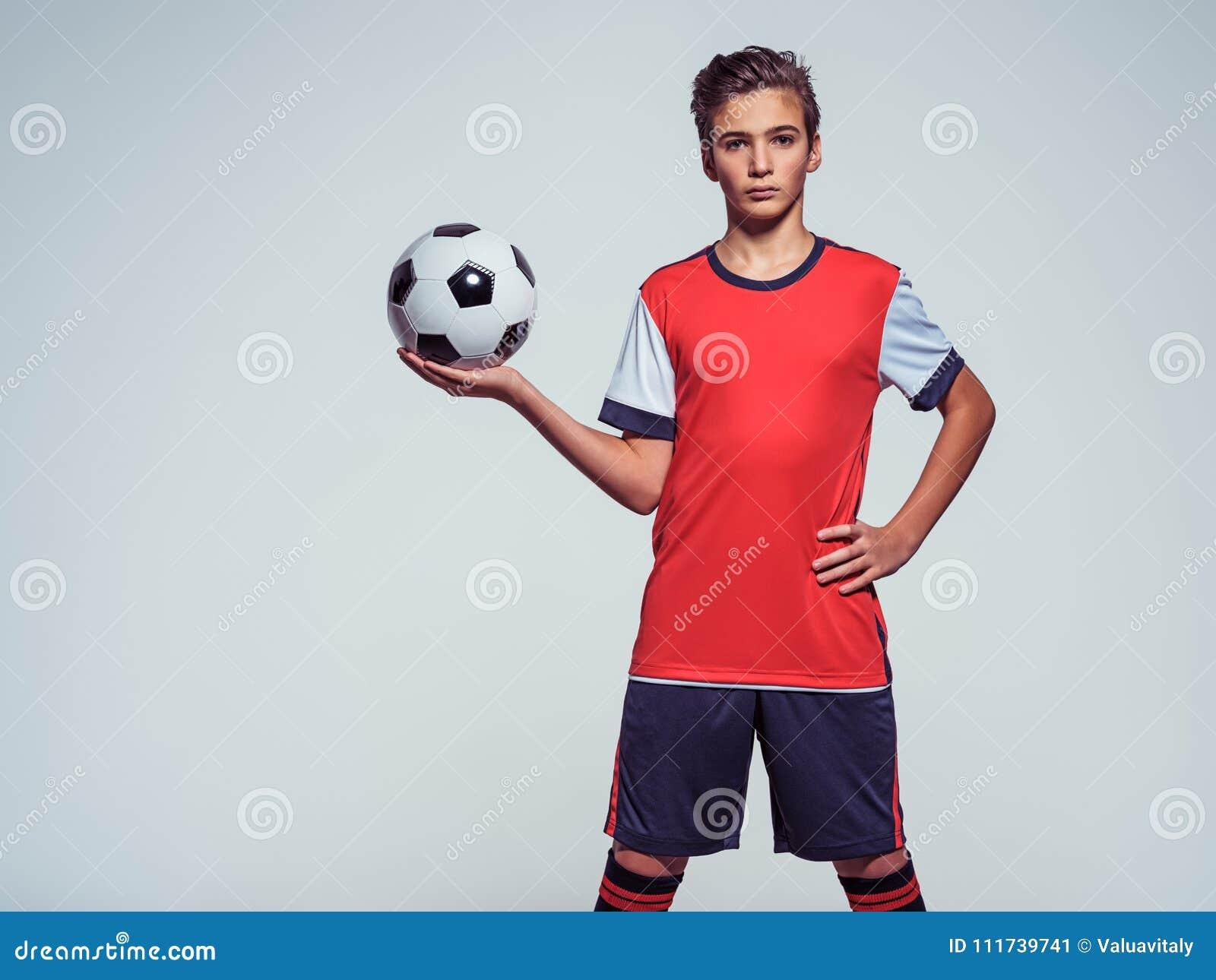 Foto des jugendlich Jungen in der Sportkleidung, die Fußball hält