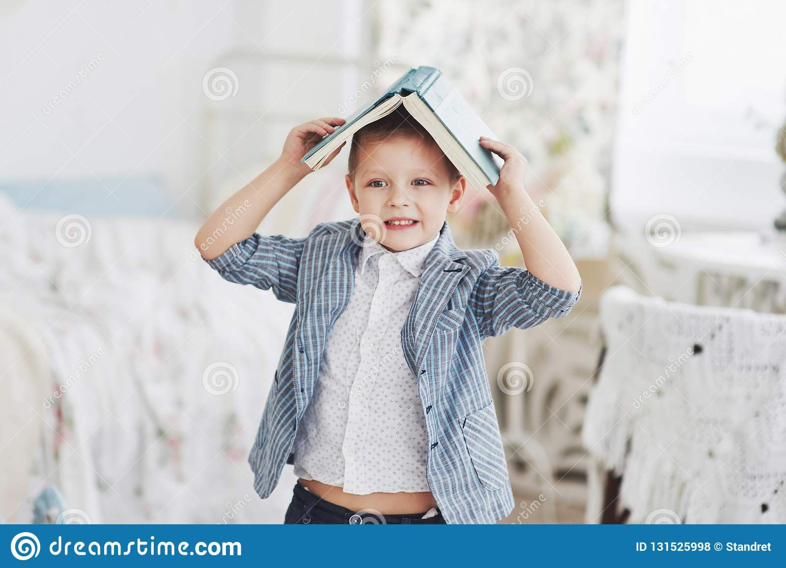 Foto des sorgfältigen Schülers mit Buch auf seinem Kopf, der Hausarbeit tut Der Schüler ist vom Handeln von Hausarbeit müde