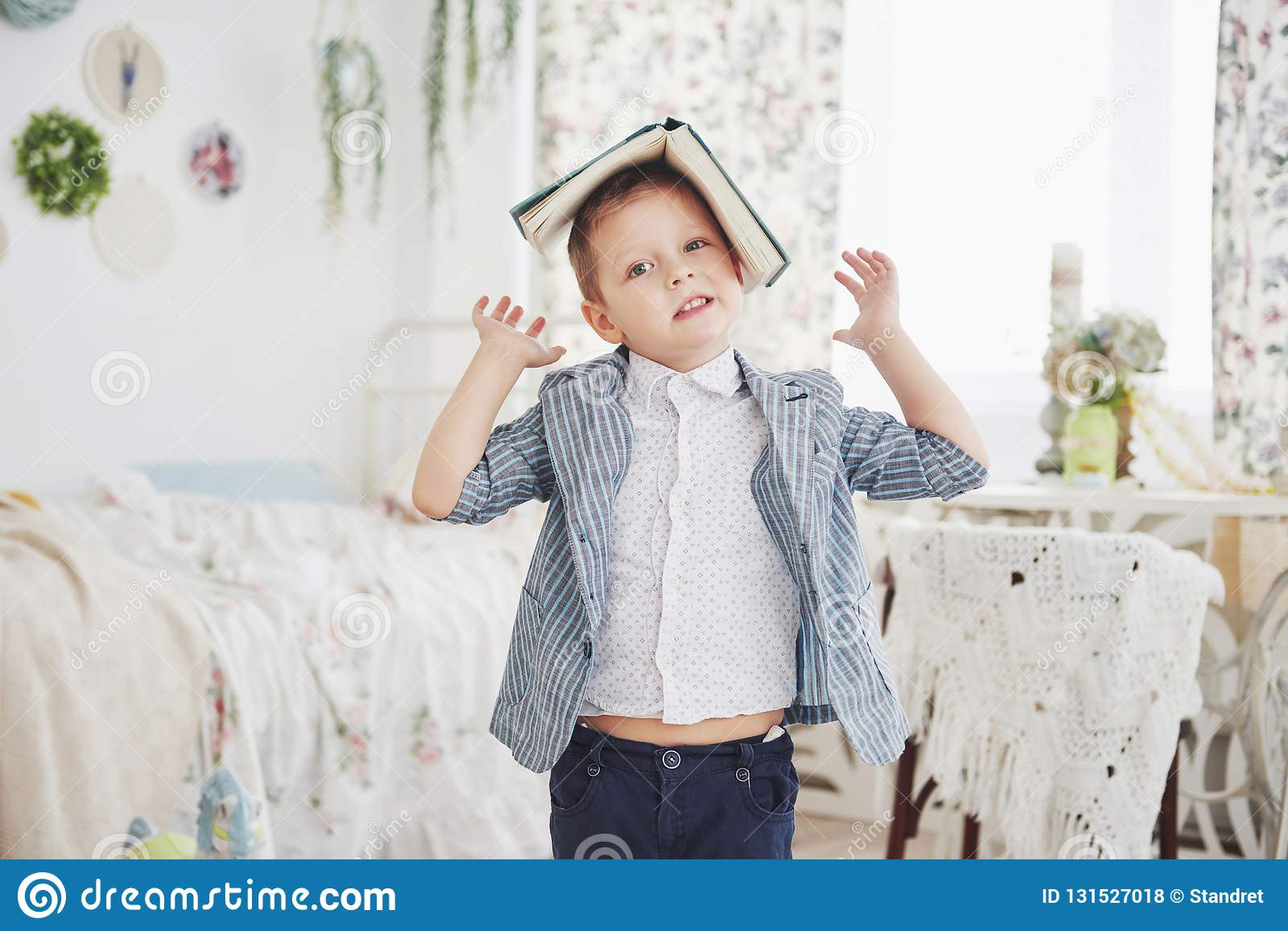 Foto des sorgfältigen Schülers mit Buch auf seinem Kopf möchte nicht studieren und gehen zu schulen Der Schüler ist von müde