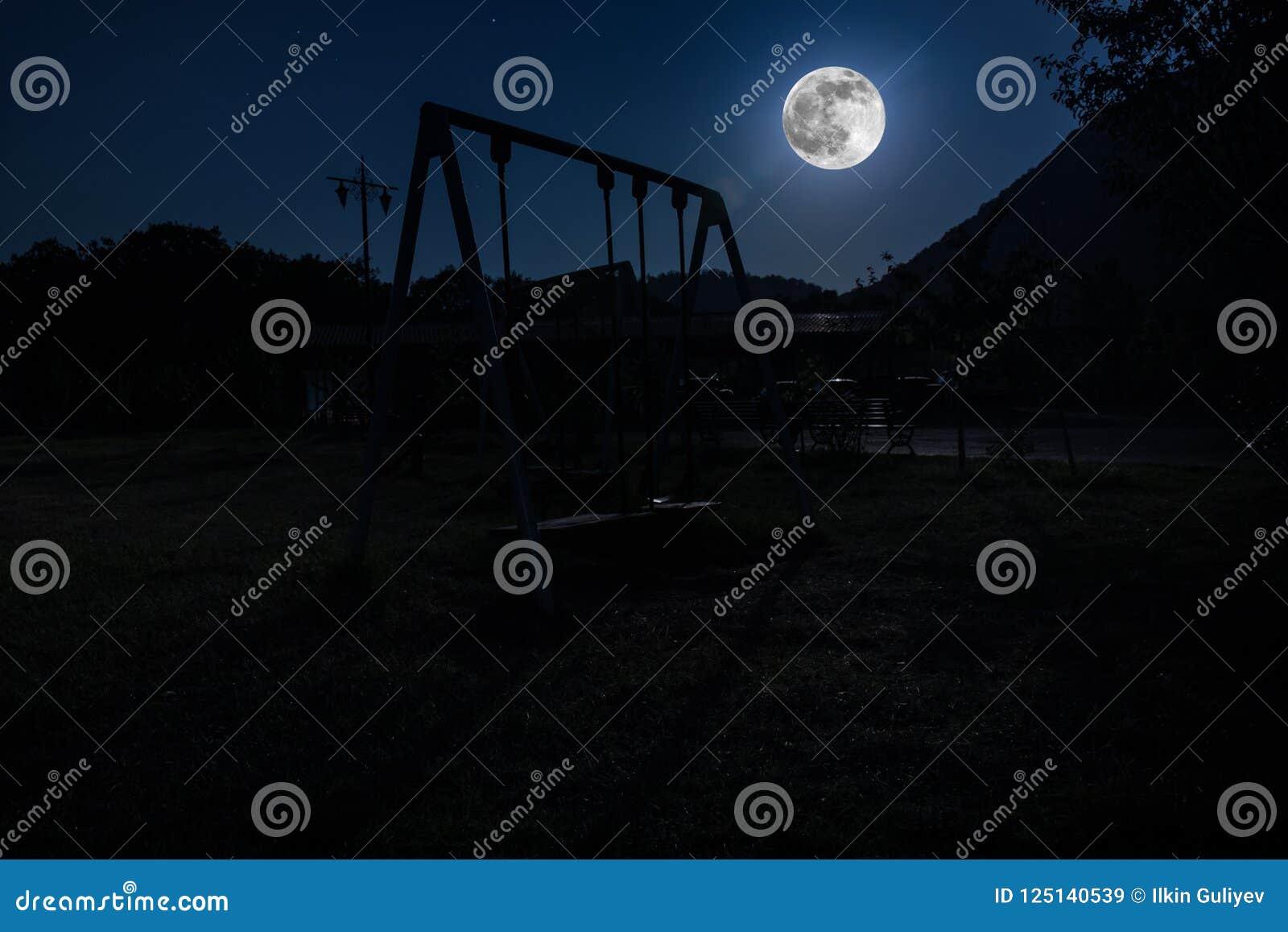 Foto di notte dell oscillazione del metallo che sta all aperto alla notte con la luna Nessuno là