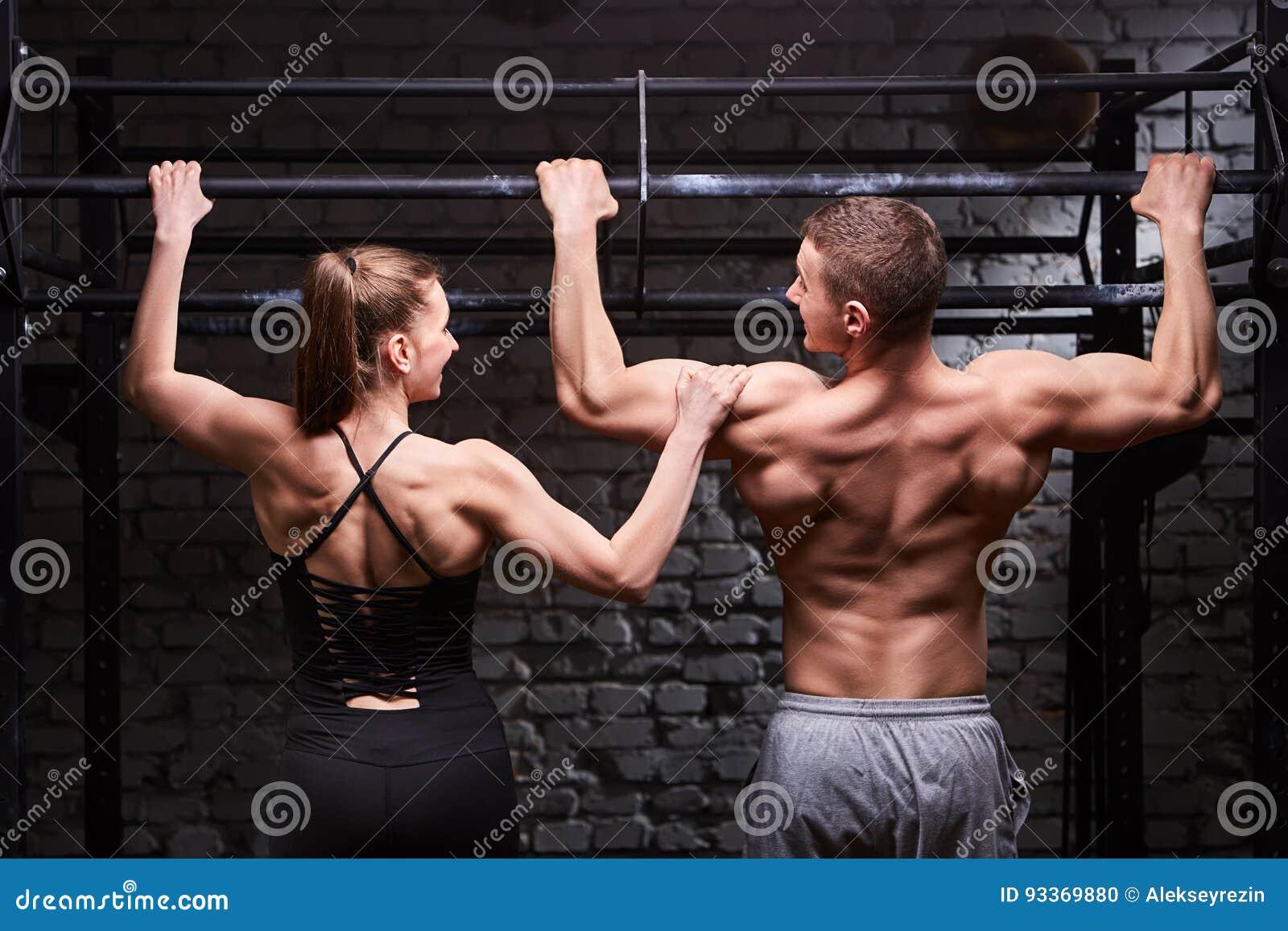 Foto di retrovisione delle coppie dell uomo e della donna nello sportwear che fa esercizio su una barra orizzontale contro il mur