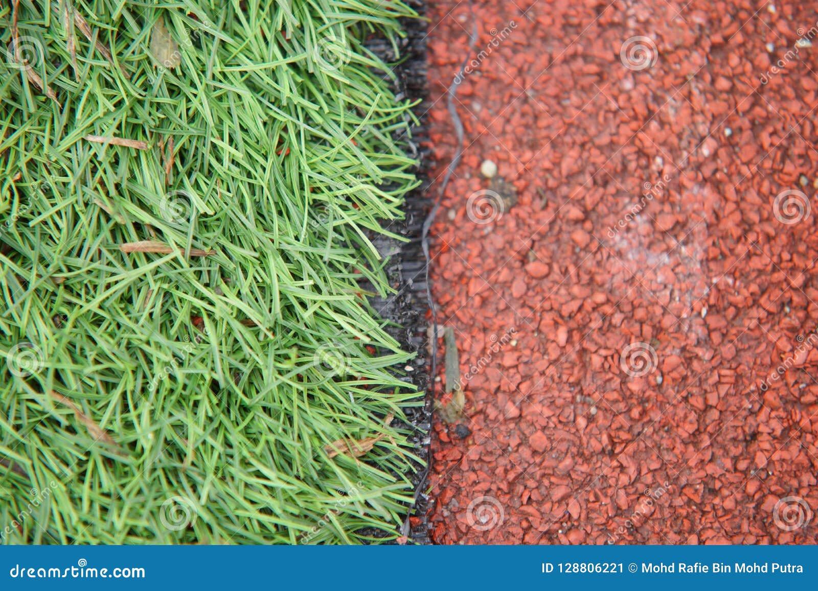 A foto do atletismo artificial do close up com grama verde combinou com a grama artificial