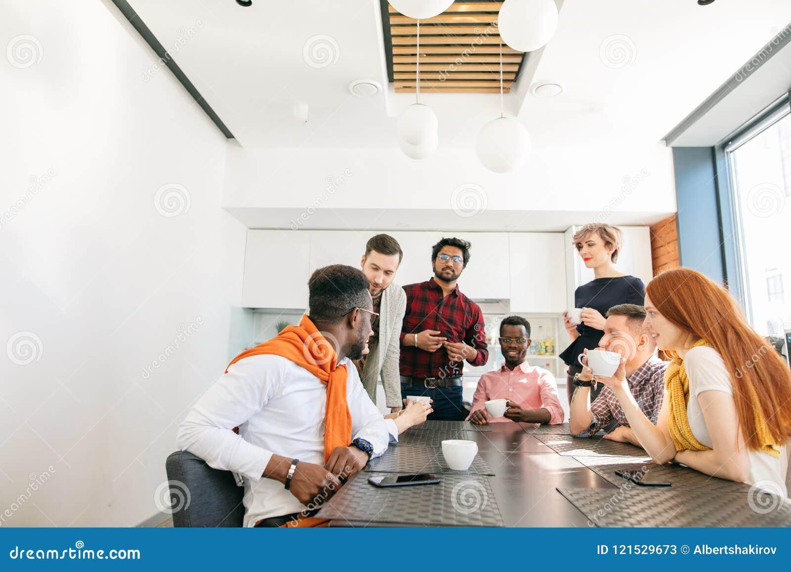 Foto do close up da equipe nova do negócio que tem a conversação dentro