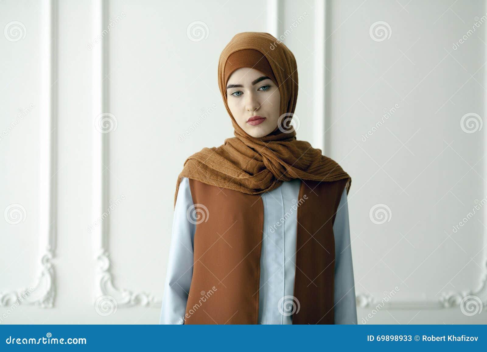 A foto do estúdio de uma jovem mulher bonita vestiu oriental datilografa dentro o estilo muçulmano