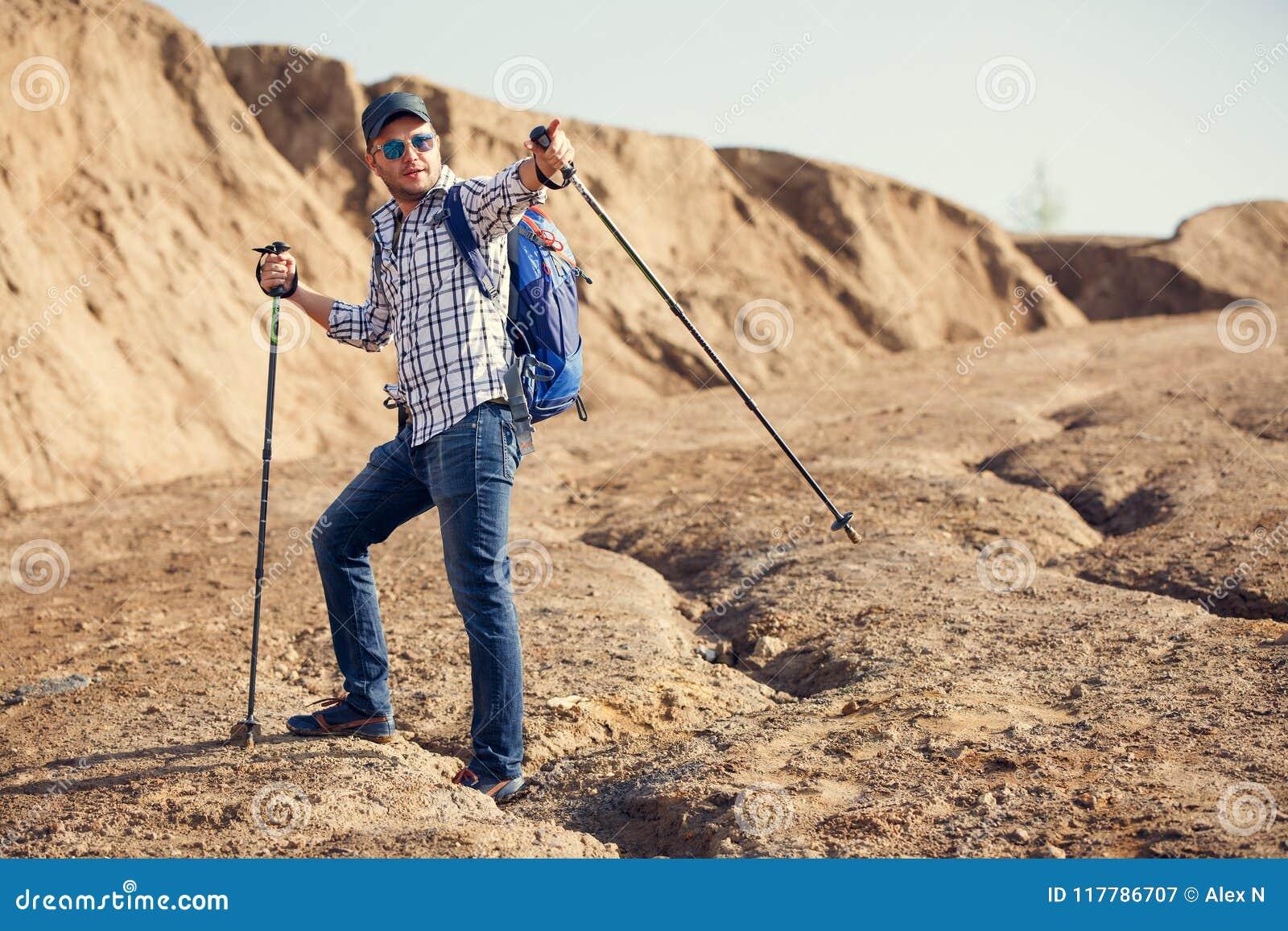 Foto do homem de sorriso do turista que aponta a vara para andar para a frente no monte