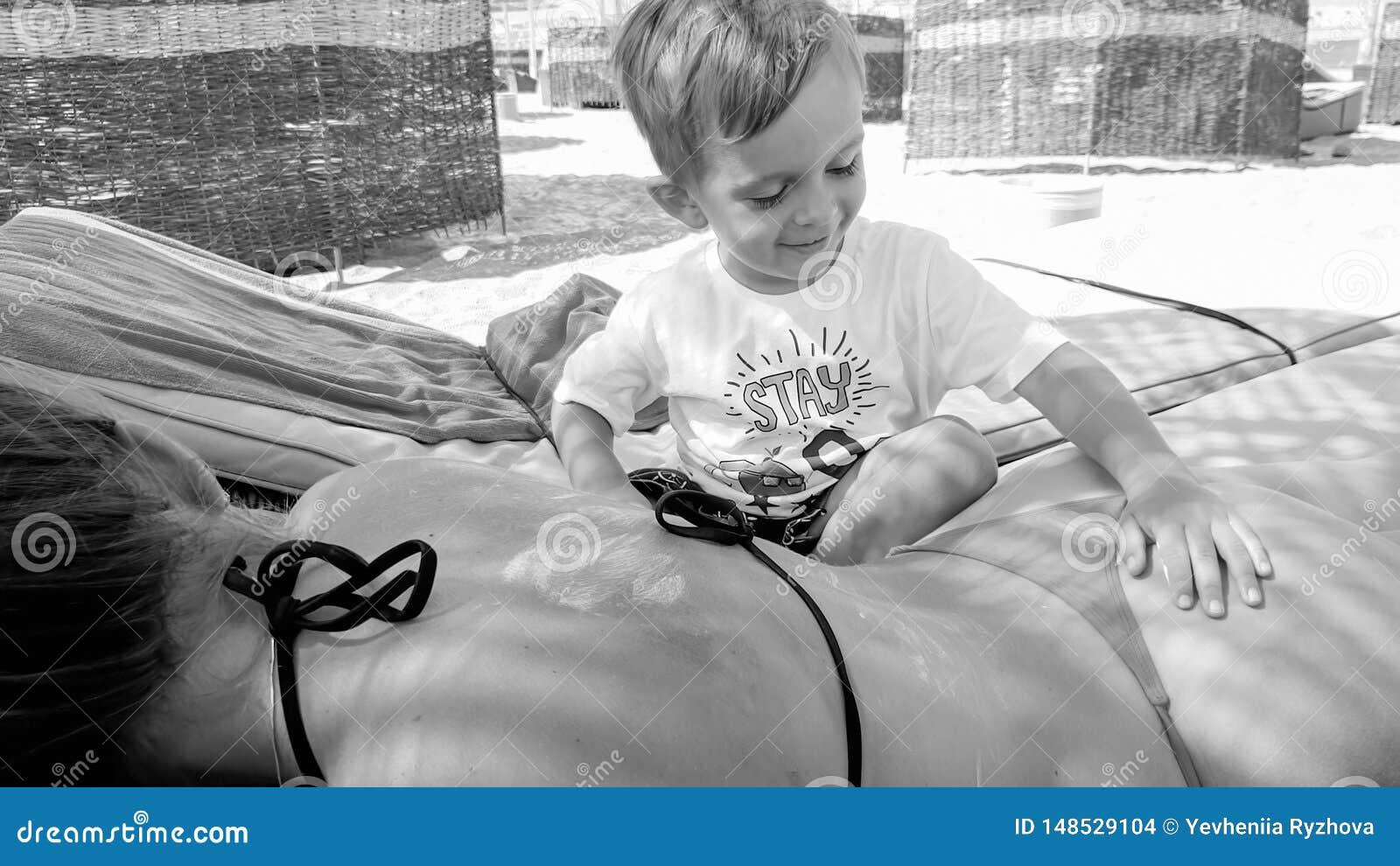 Foto do menino pequeno da crian?a que aplica o creme da prote??o solar nas m?es que encontram-se para tr?s no vadio do sol na pra