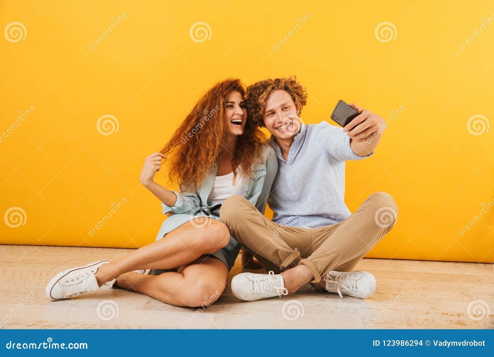 Foto do noivo feliz e da amiga 20s que sentam-se no assoalho a