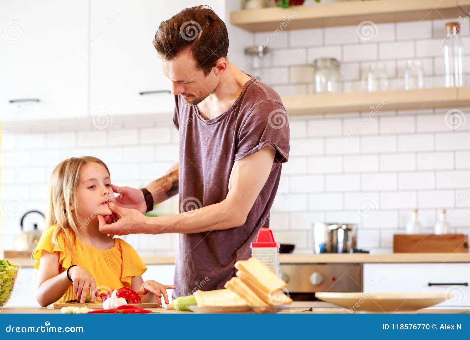 Foto do pai novo com a filha que cozinha o lunchn