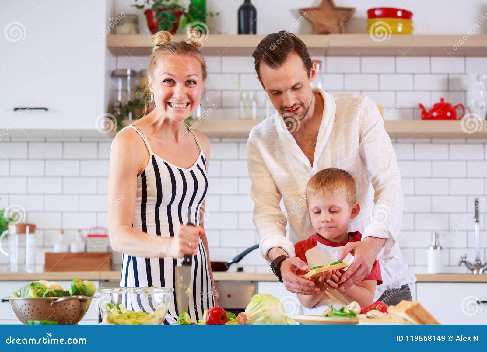 Foto dos pais e do filho novo que preparam o alimento na cozinha