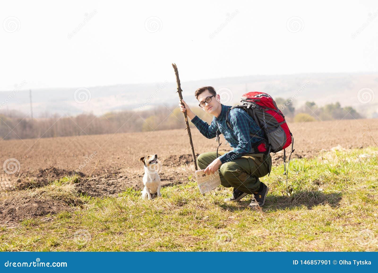 Foto eines jungen Touristen und seines Hundes, gehend in die Landschaft