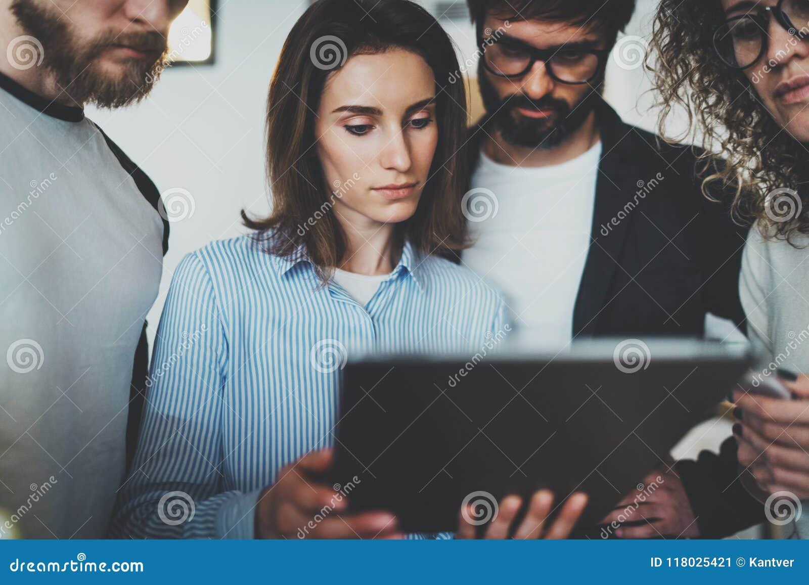 Foto för Coworking lag tillsammans Grupp av unga coworkers som använder det elektroniska handlagblocket på den moderna kontorsvin