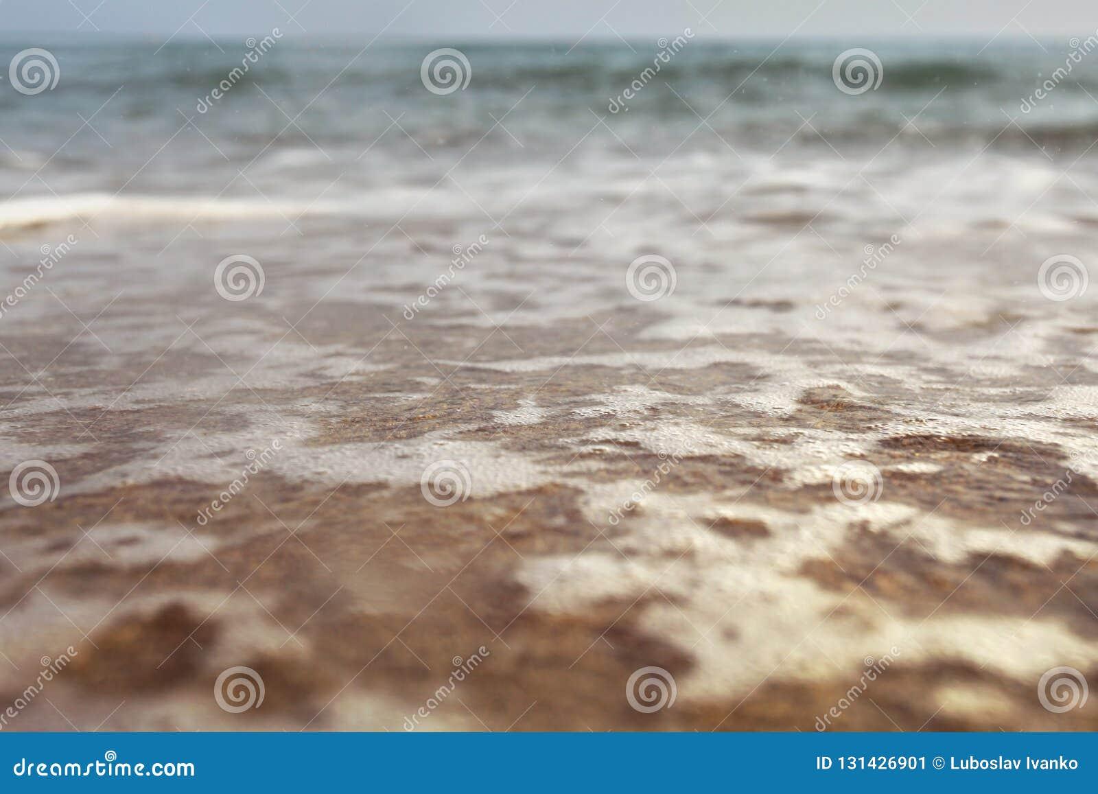 Foto för låg vinkel från markplanet - strand med grunt vatten och vitt skum över sand, våta droppar i luft, suddigt hav i avstånd