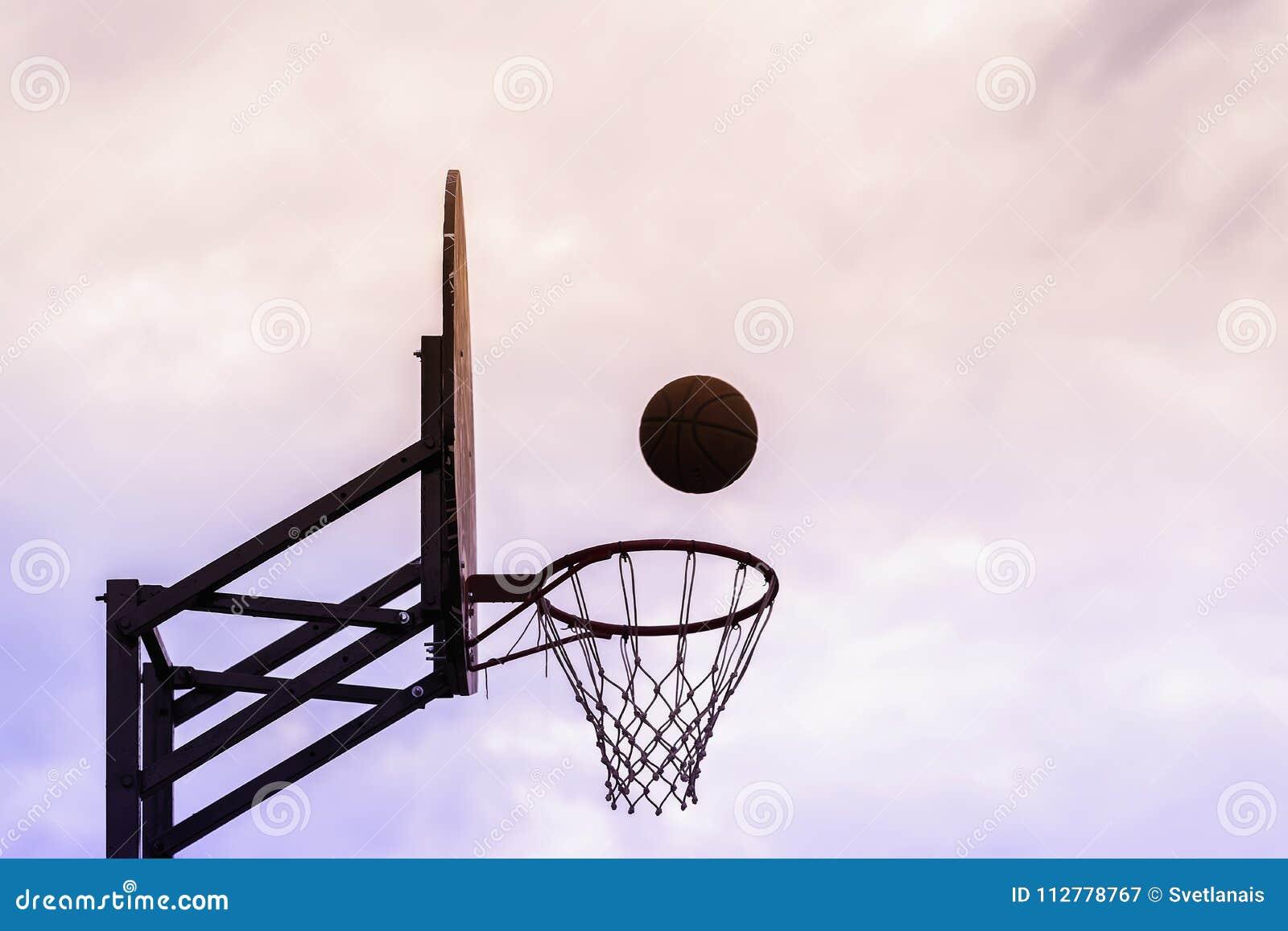 Foto gráfica do protetor do basquetebol, bola que voa à cesta no fundo do céu Conceito do esporte, precisão batida cópia