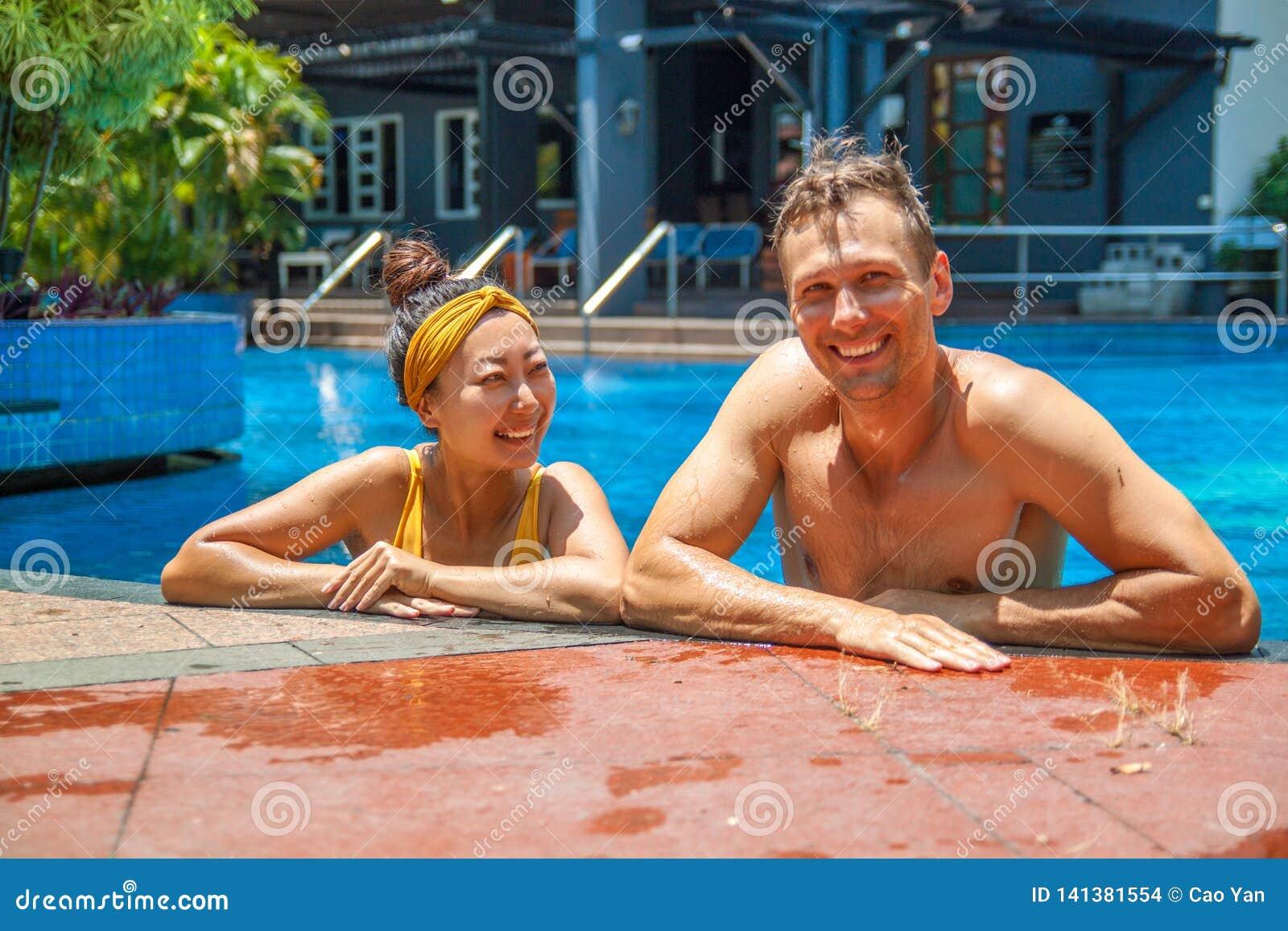 Foto hermosa de pares felices en la piscina que charla con uno a