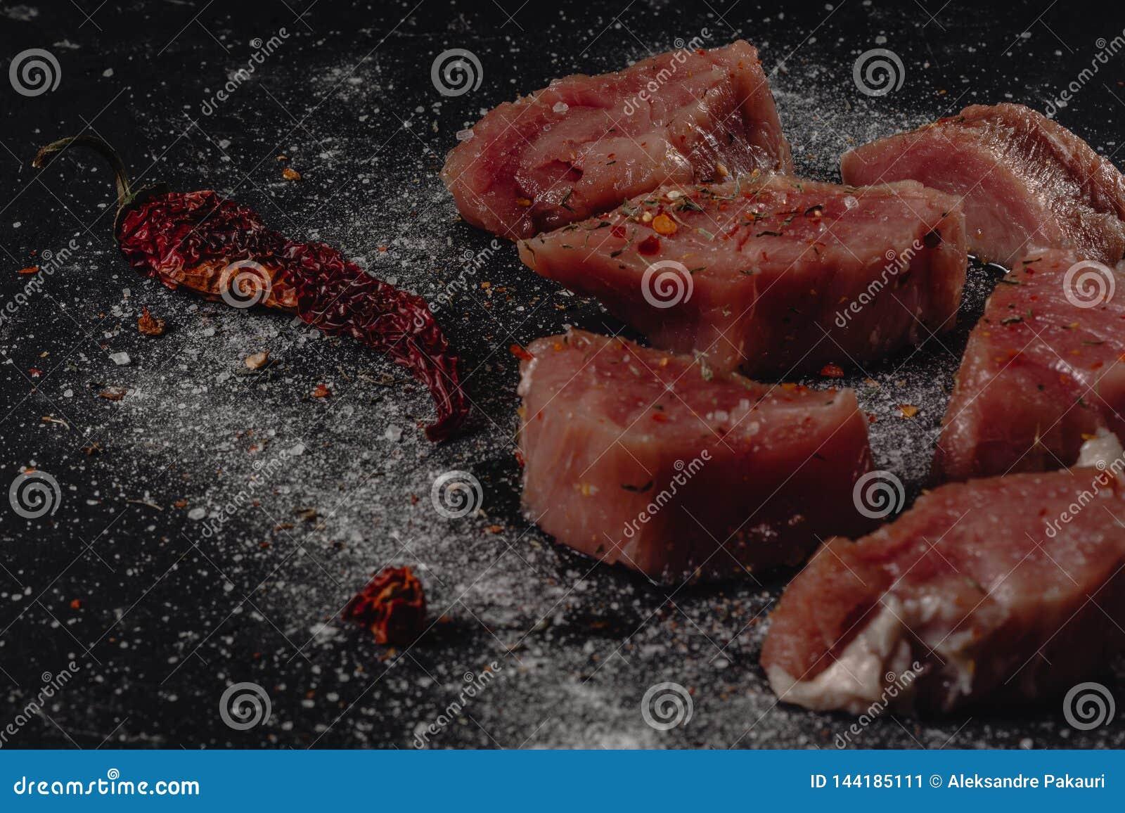 Foto horizontal de la carne cruda del filete de cerdo La carne cruda está en tablero oscuro rústico del bastón, con pimienta y sa