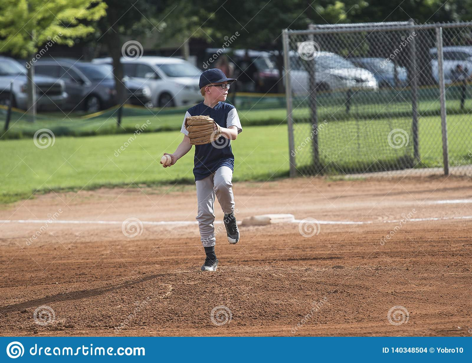 Foto integral de la acción de una jarra del béisbol de la liga pequeña que lanza una echada