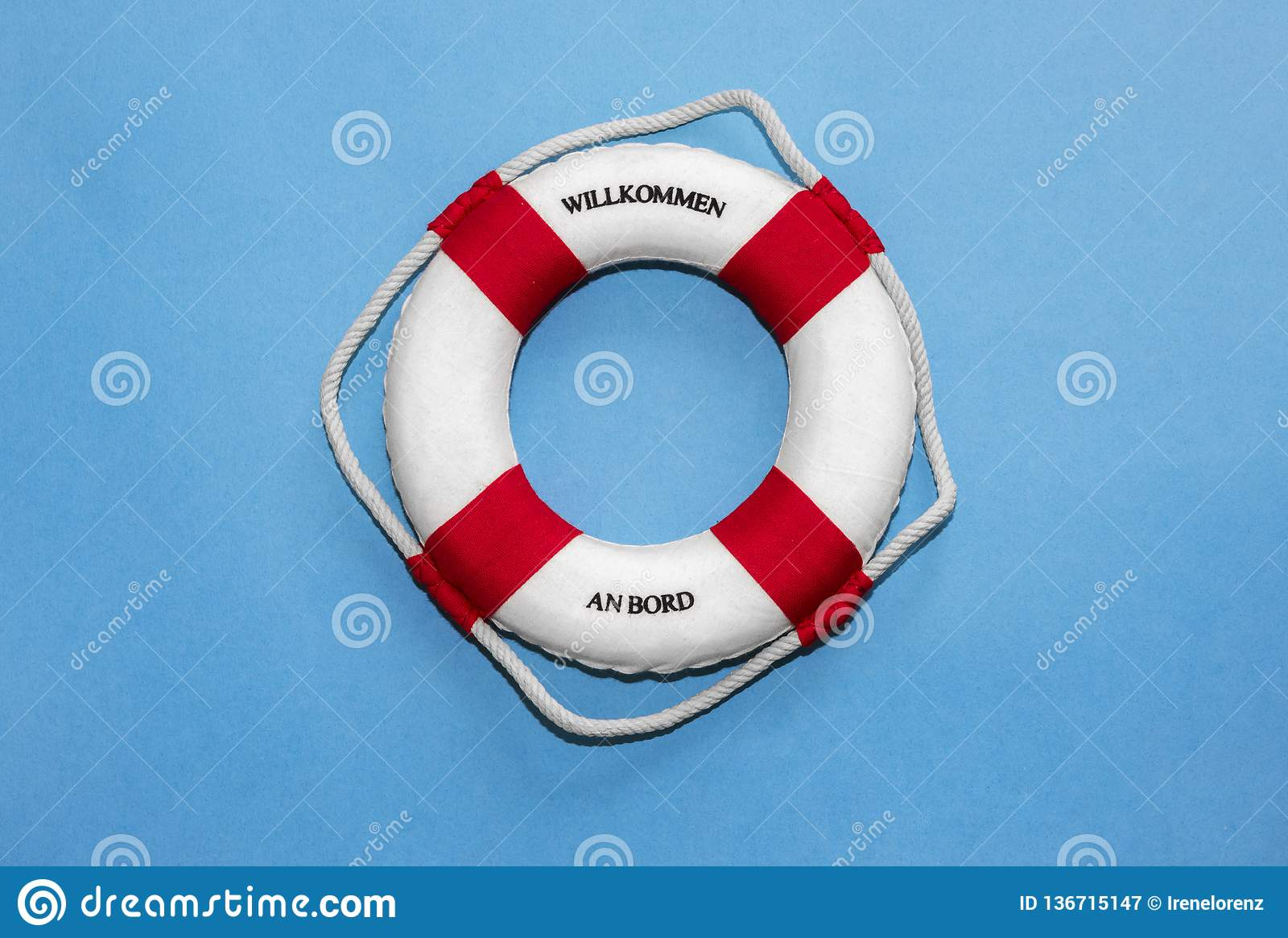 Lifebelt with lettering `Willkommen an Bord` in german language translates to `Welcome on board` on blue paper background