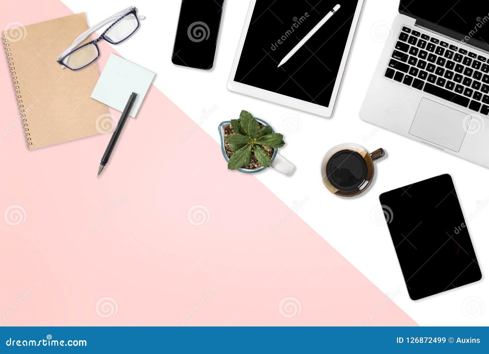 Foto lisa da configuração da tabela do escritório com laptop, a tabuleta digital, o telefone celular e os acessórios em um branco