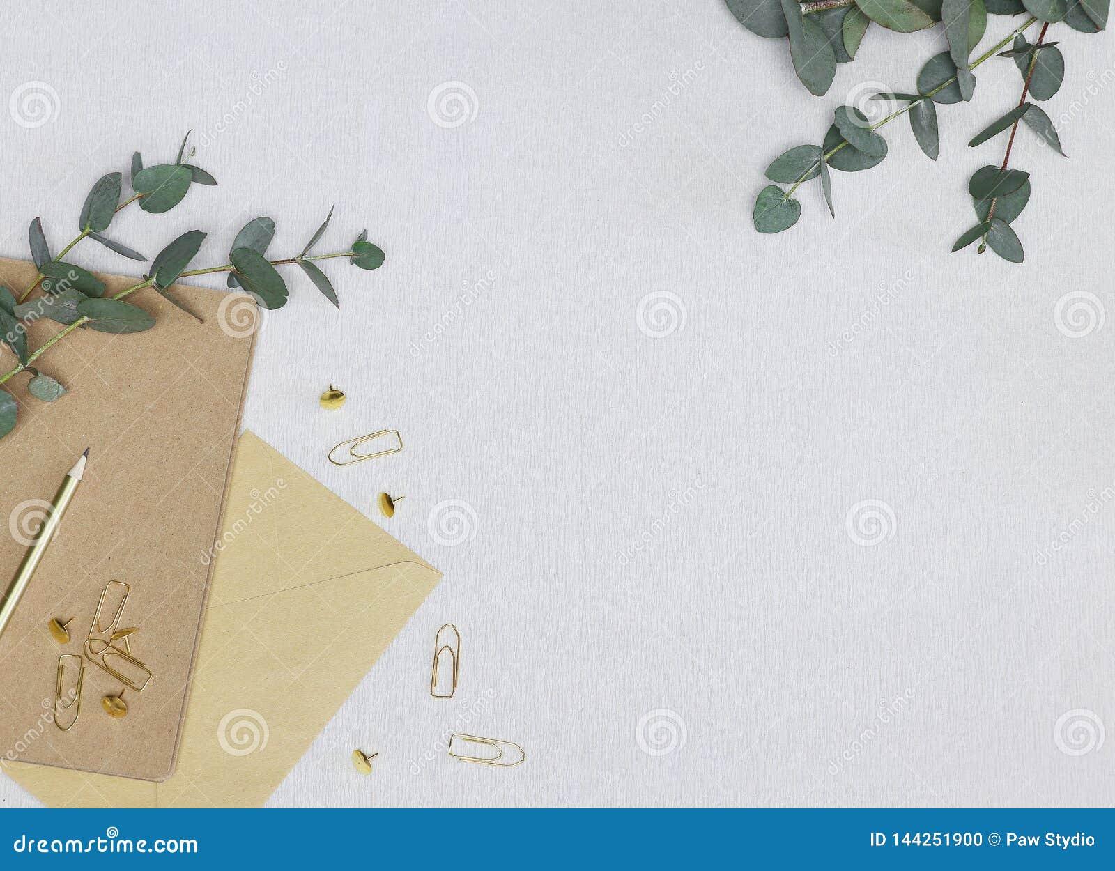 Foto minimalista con el lápiz de oro, clips de papel, pernos, nota, sobre, ramas del eucalipto