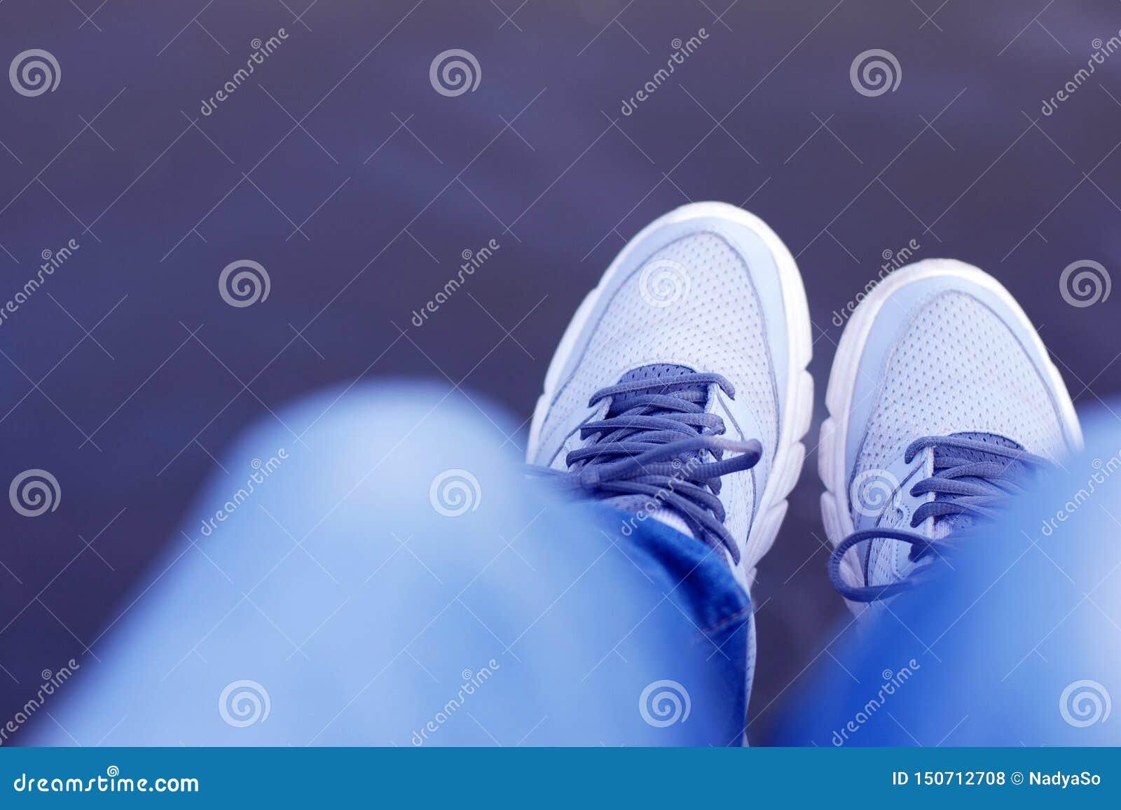 Foto: NadyaSo oscila os pés sobre a água, calças de brim, sapatilhas cinzentas, primeira pessoa